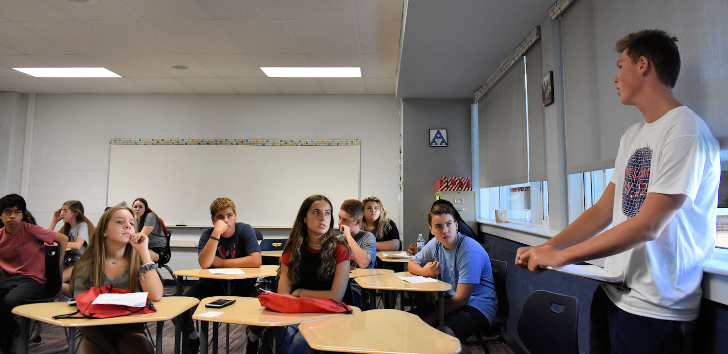 An upperclass student addresses freshman seated at desks in a classroom.