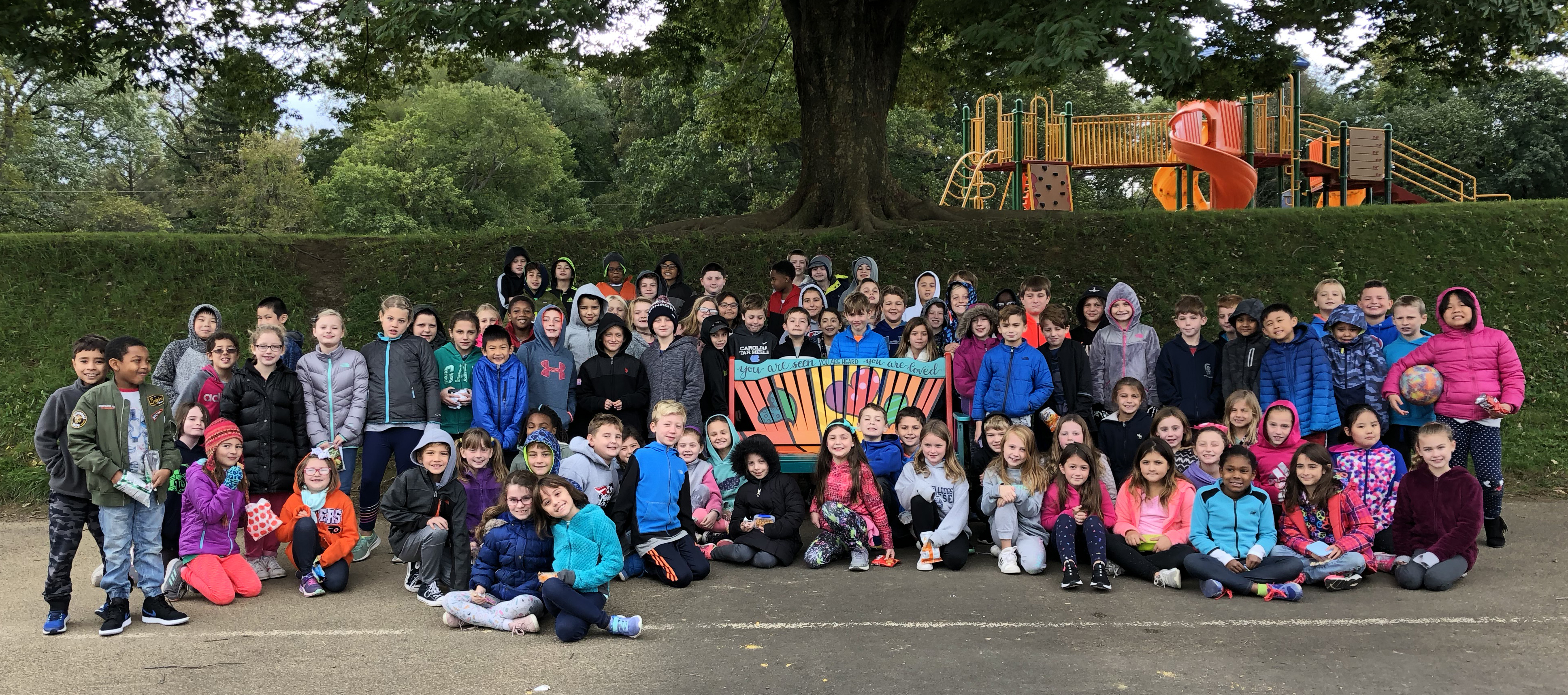 about 100 third graders standing around a colorful bench on the blacktop part of the playground