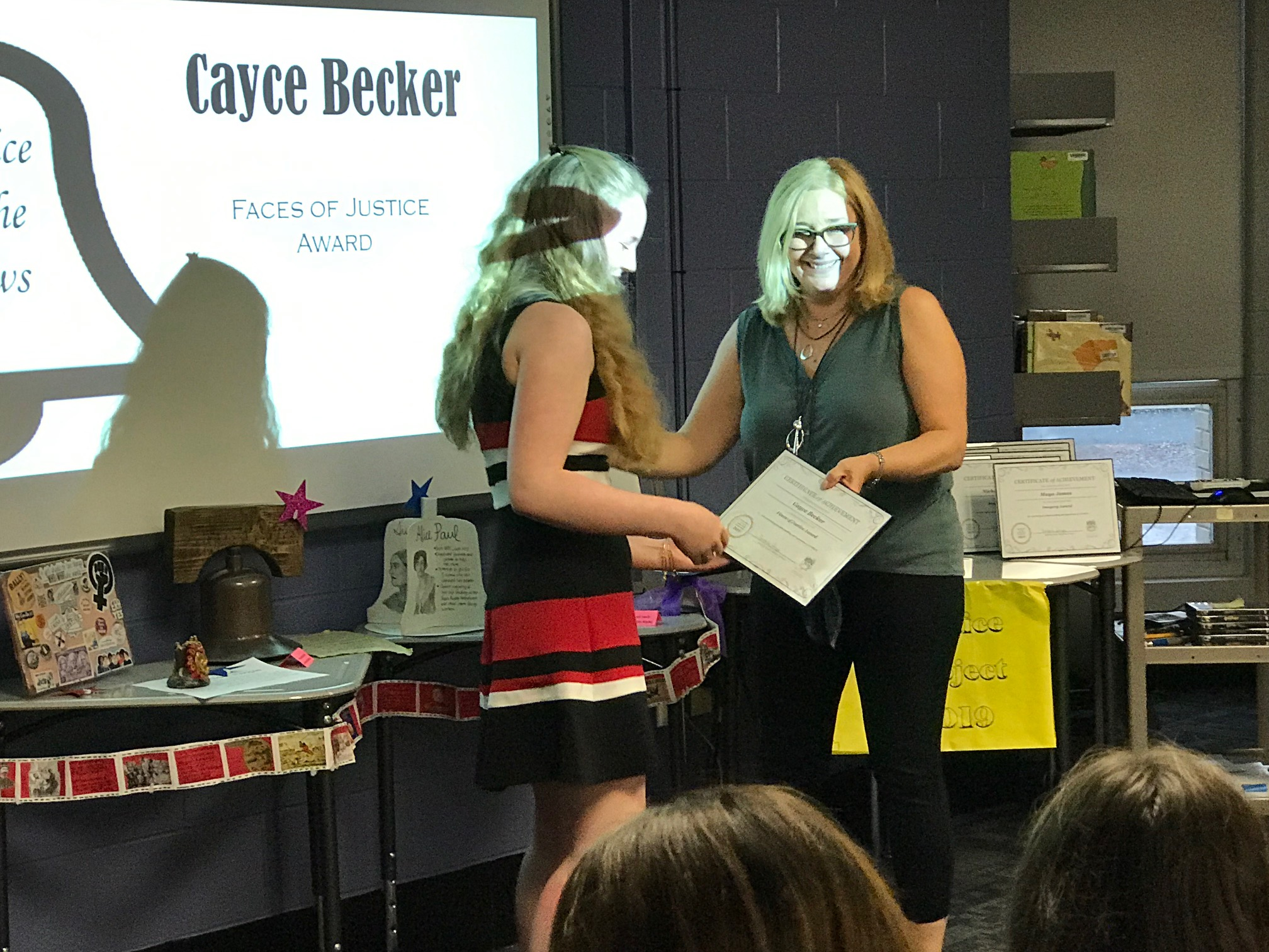 teacher presenting certificate to student