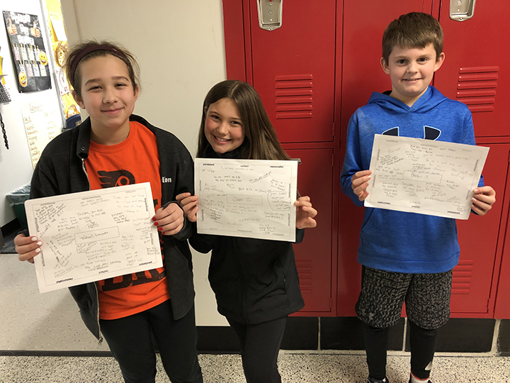 Three students holding papers with written compliments on them