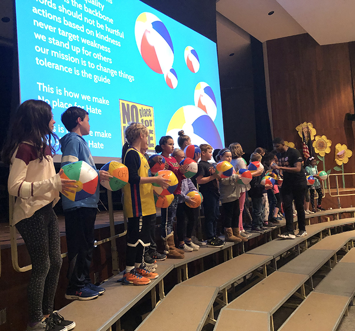 students standing in line on stage holding beach balls