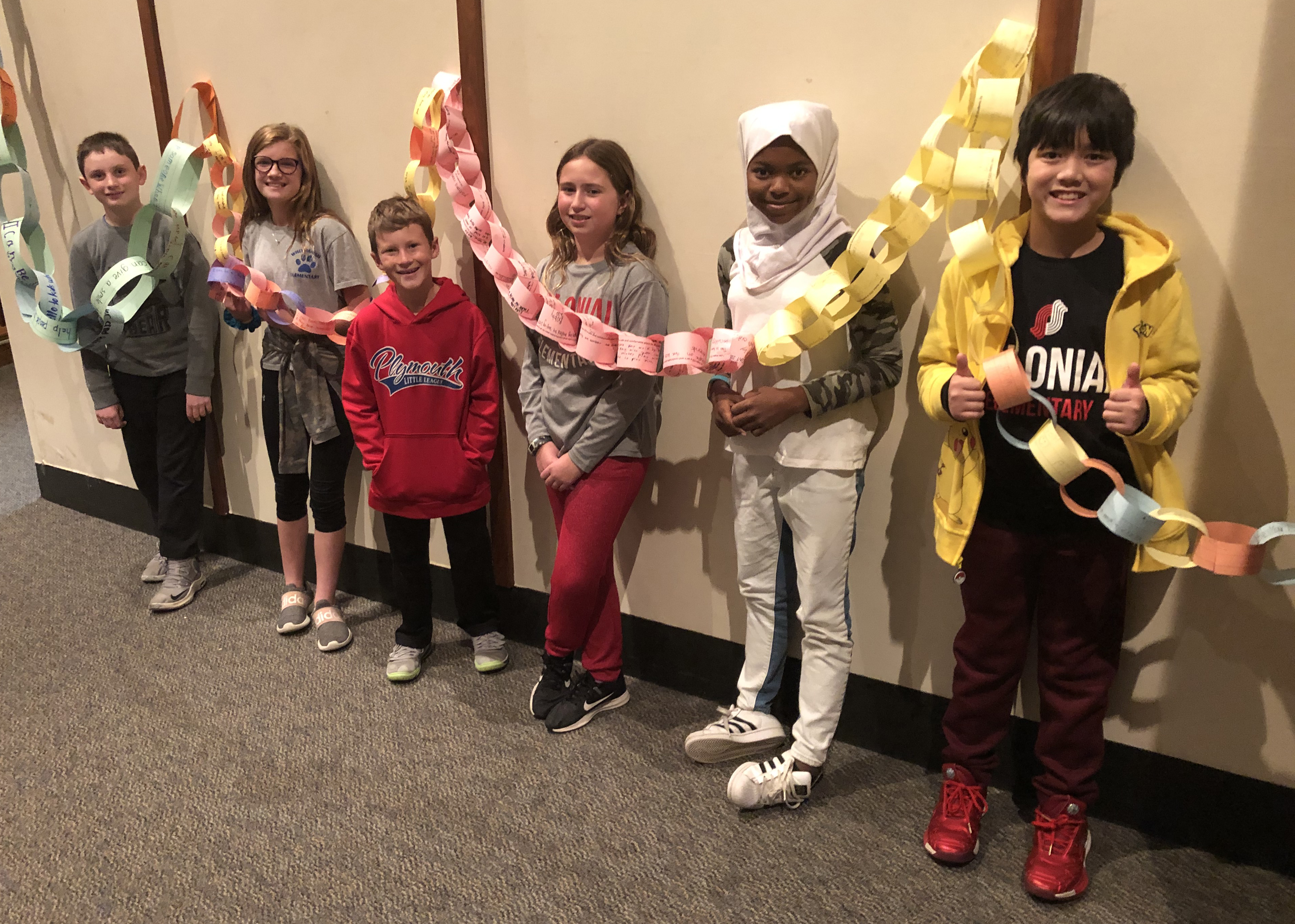 Six students with a long paper chain.