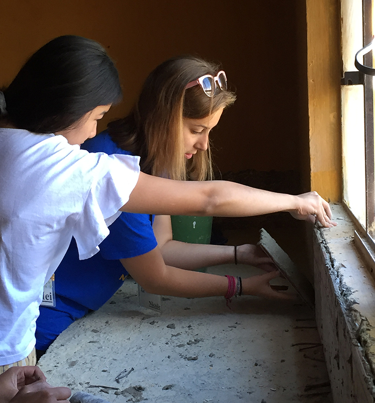 Two girls cementing a tile