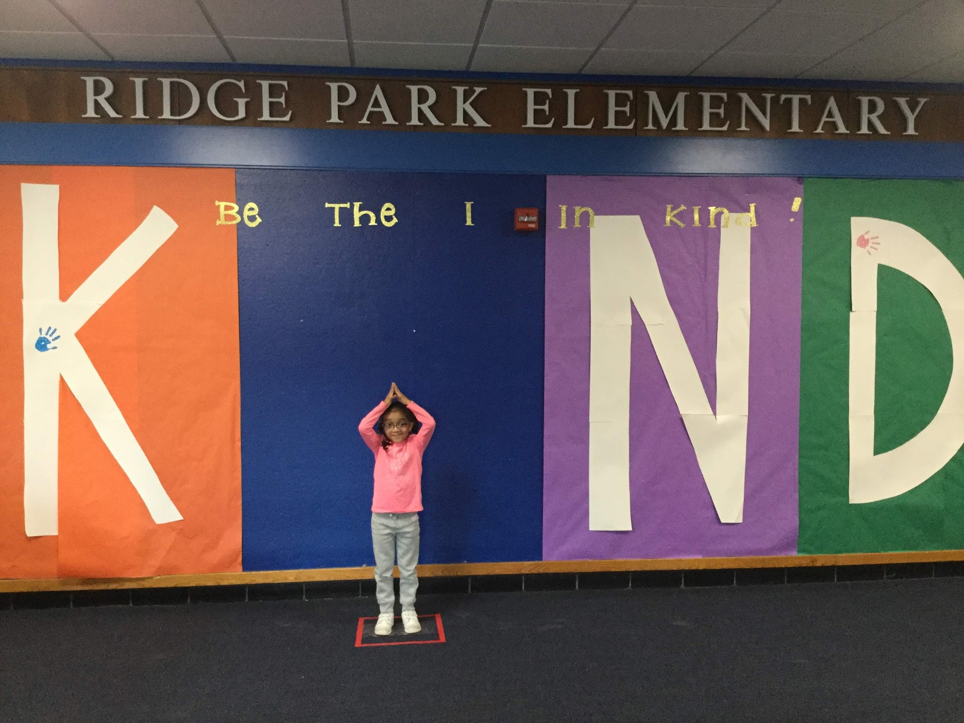 Girl makes letter I in large word Kind on wall