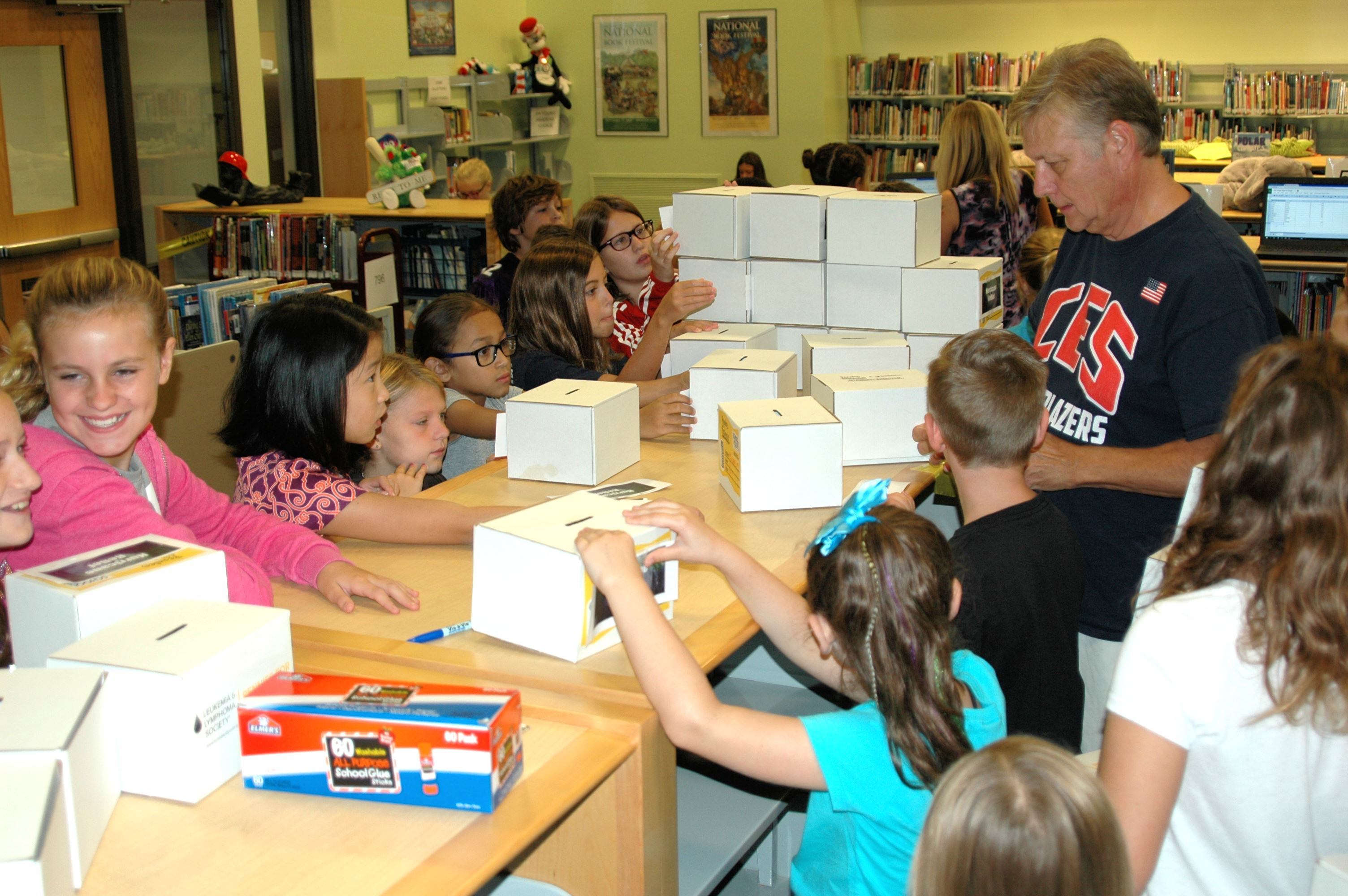 Several students working with Teacher Ken Grimes to fold cardboard donation boxes.
