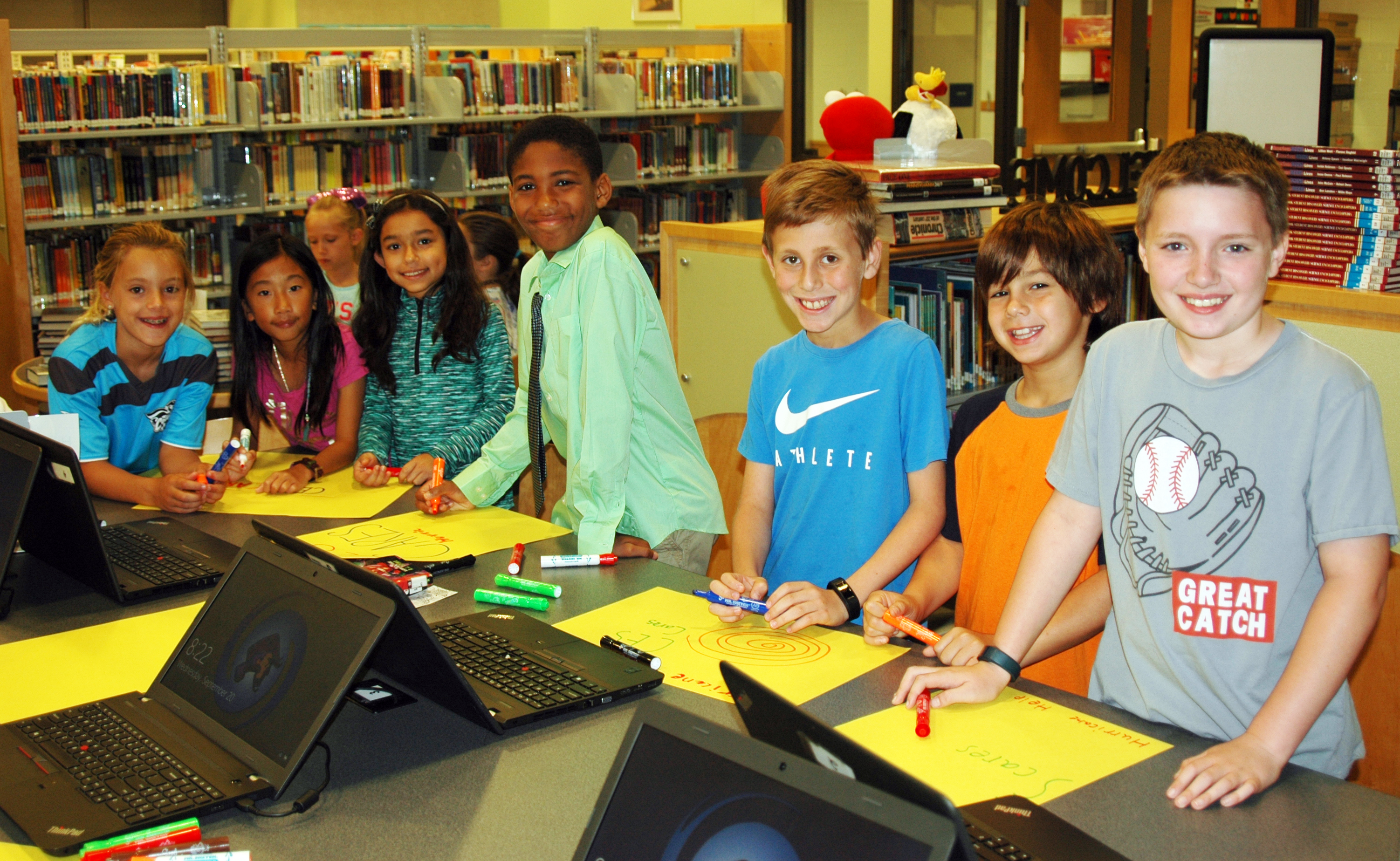 Seven elementary students taking a break from making posters with markers and construction paper to smile at the camera.