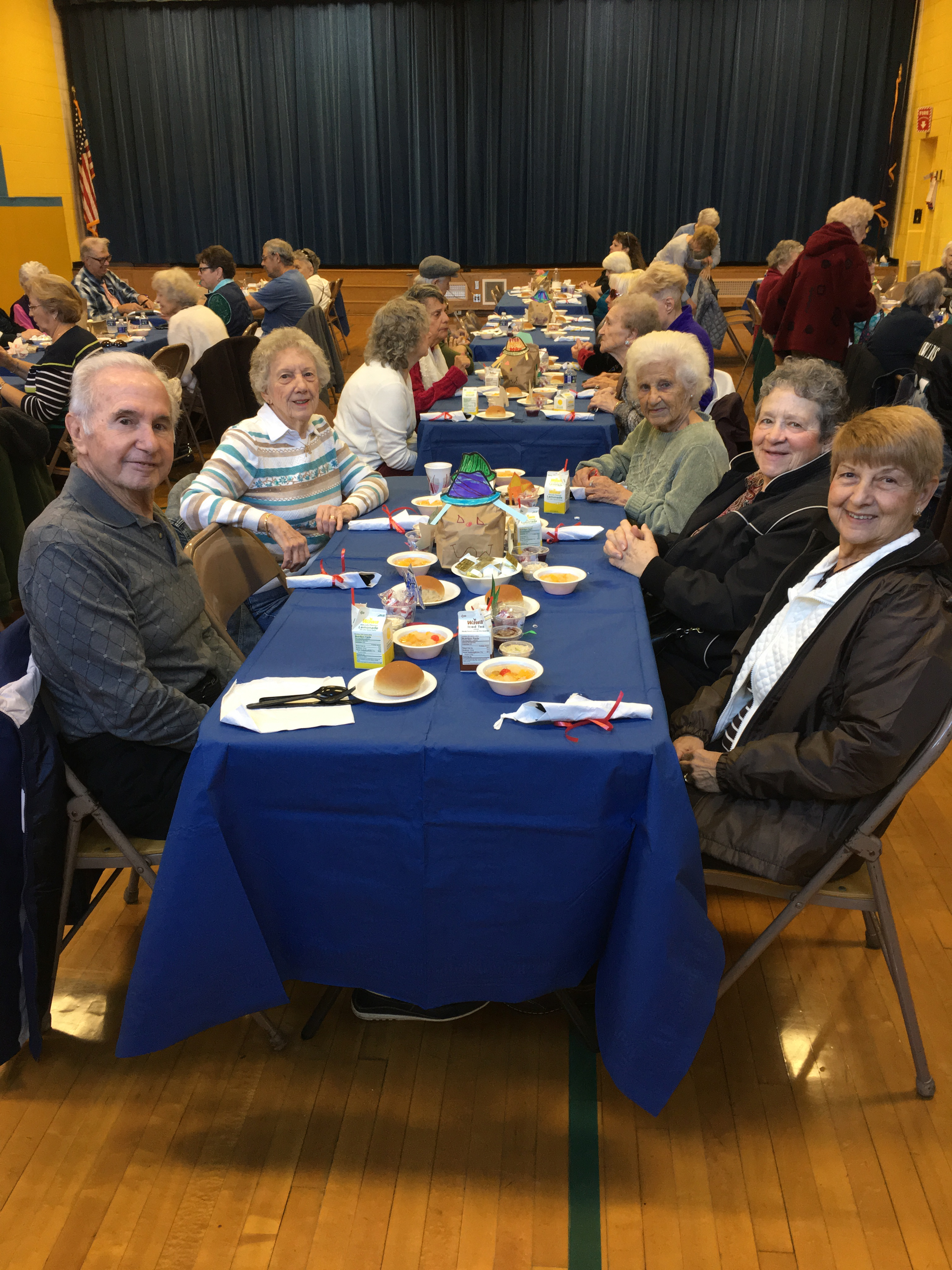 Seniors citizens seated at a table set for dinner smiling at the camera.