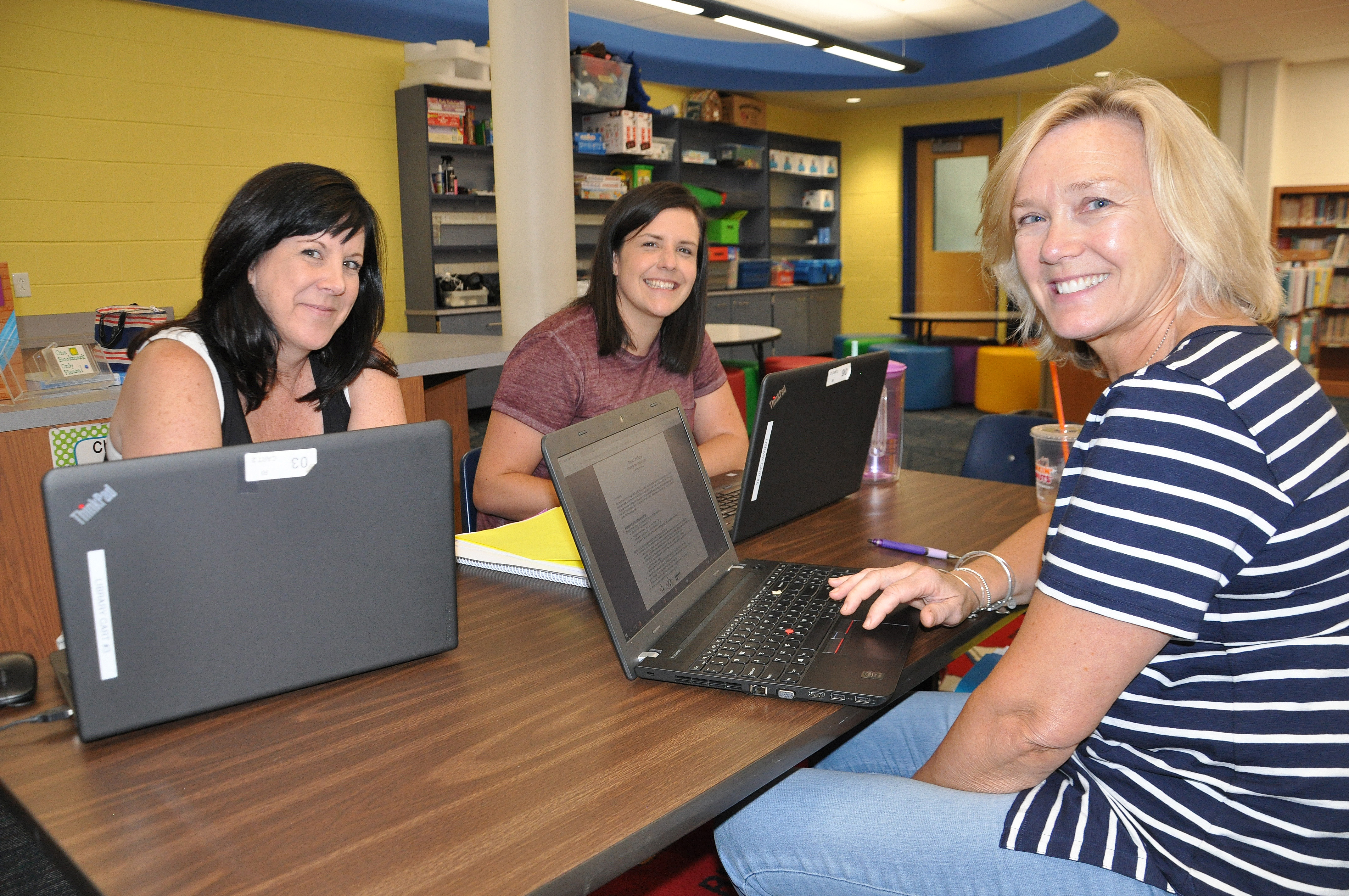 Three teachers working on laptops at a table in the Ridge Park library.