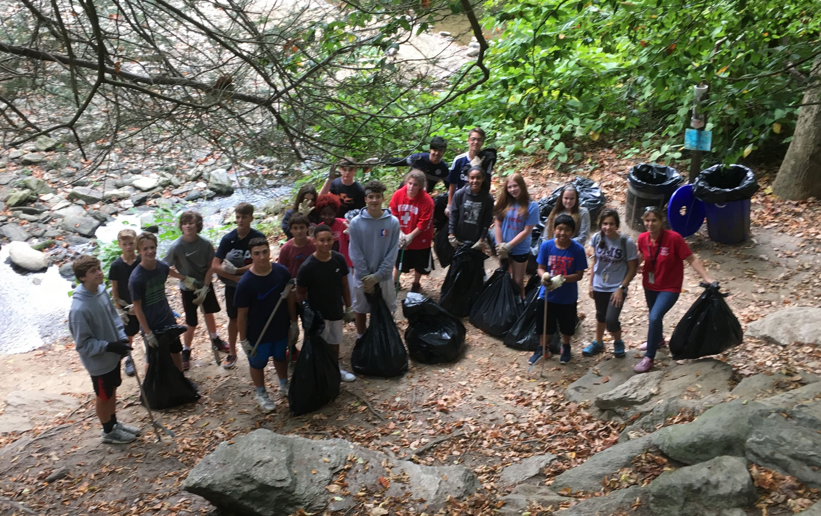 Approximately 15 students in the woods near the edge of water with trashbags