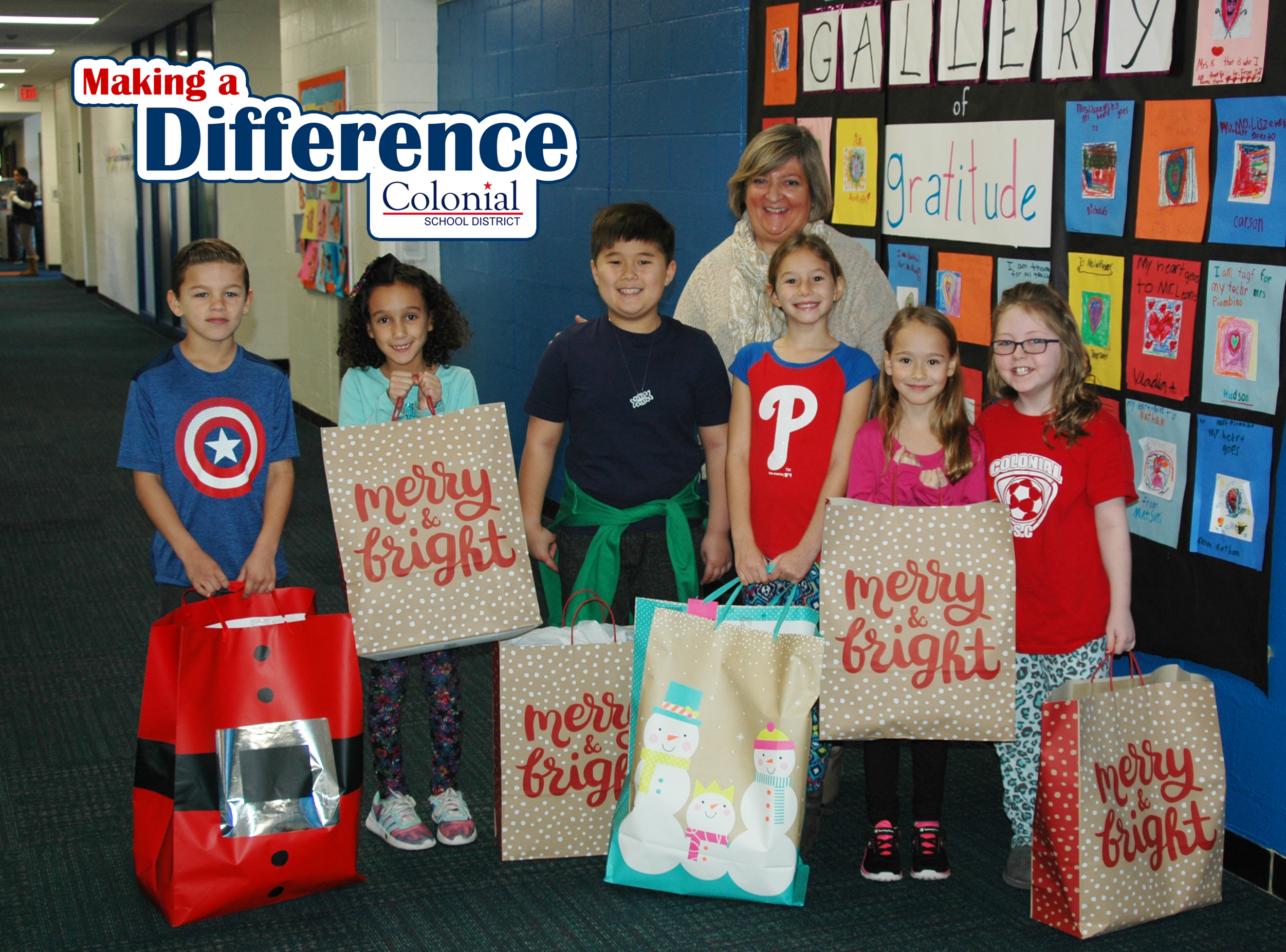 Six students and a teacher holding holiday gift bags.