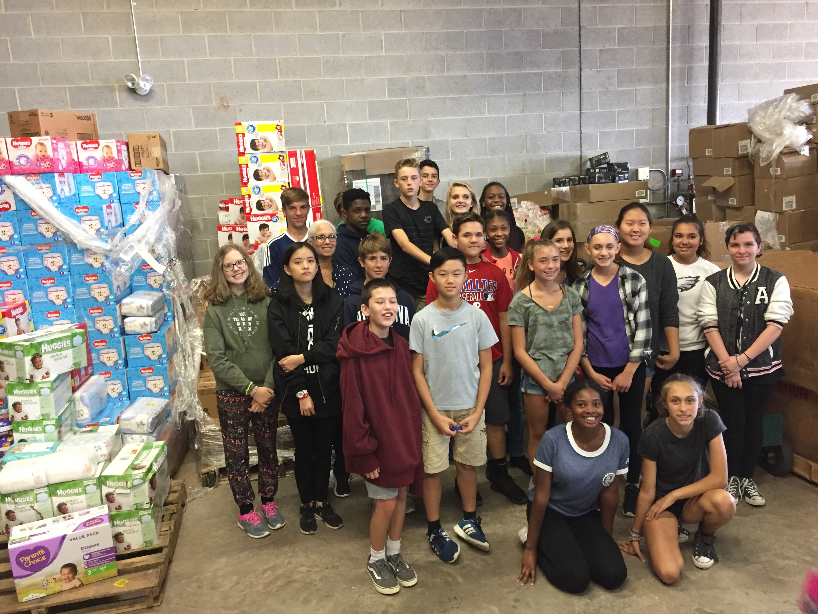Group of approximately 20 kids in a warehouse