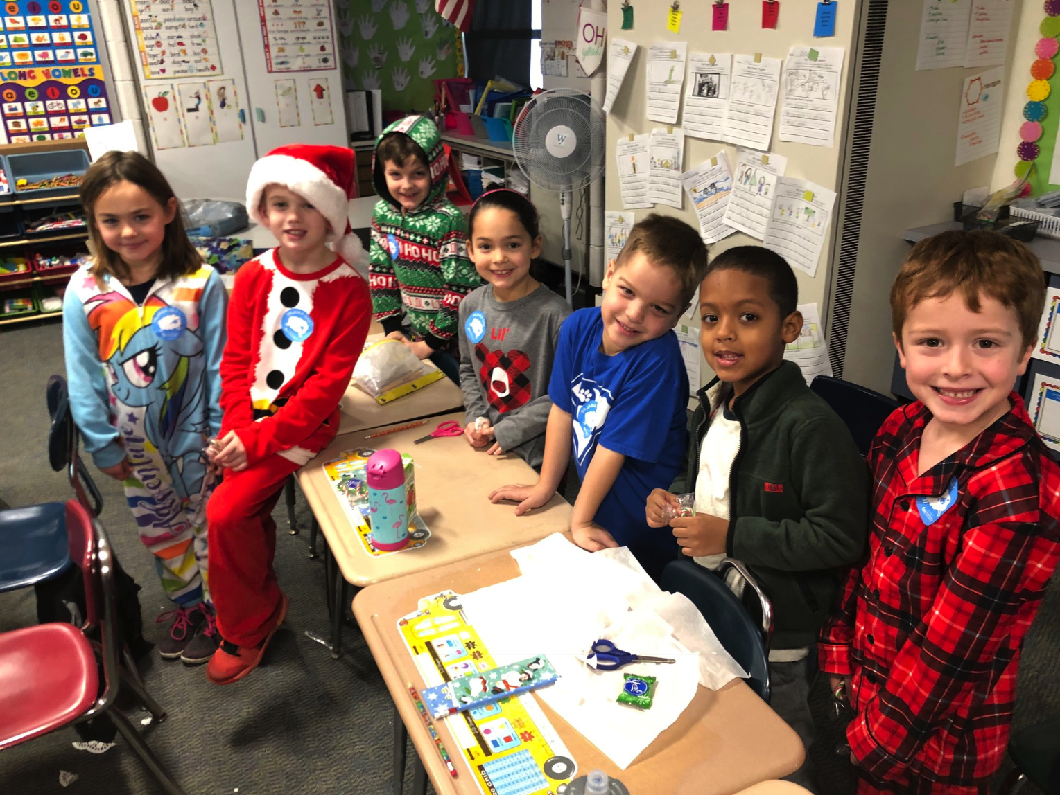 seven children wearing their pajamas in a classroom