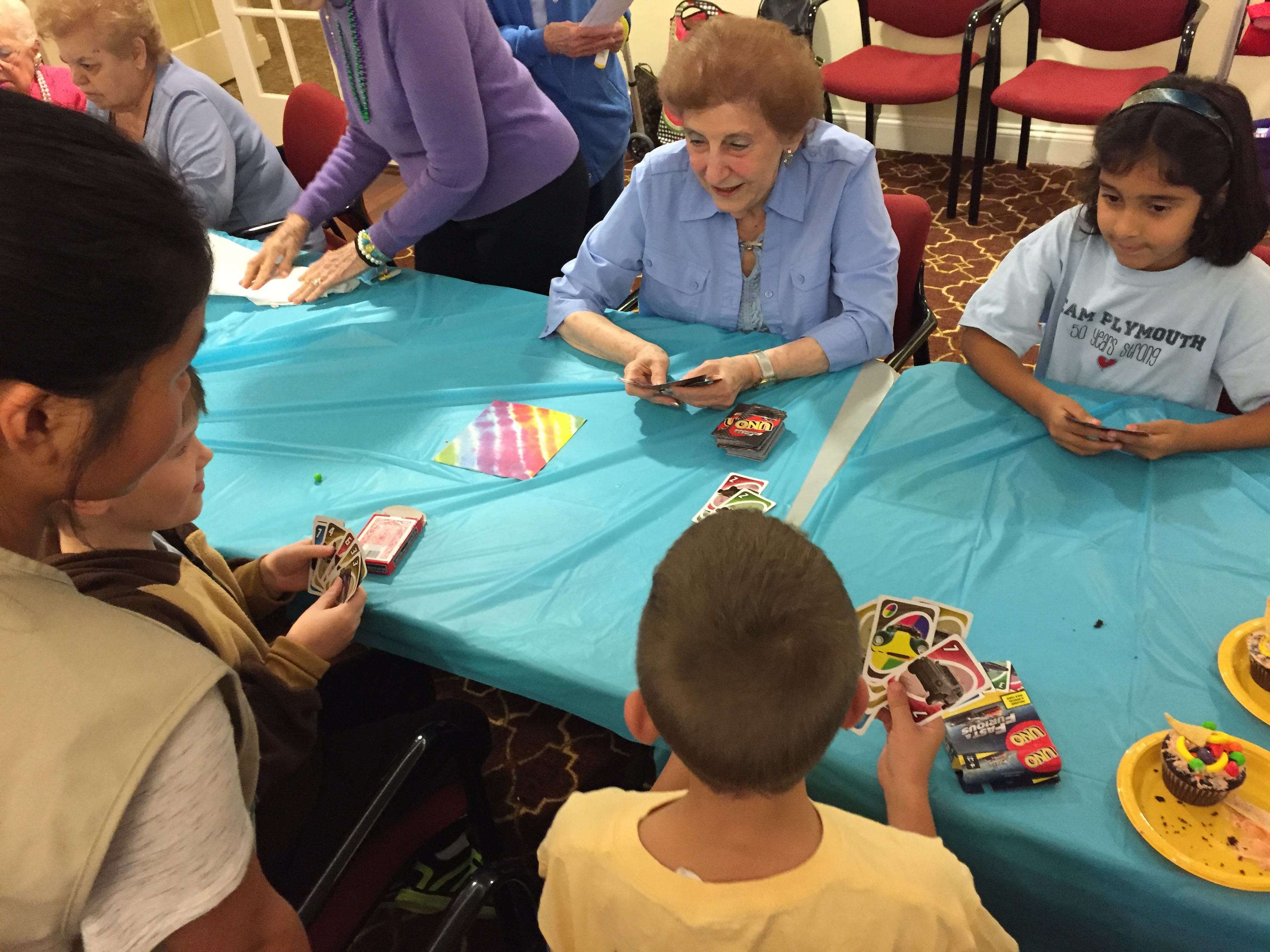 Three students and a senior play uno while a Girl Scout watches.