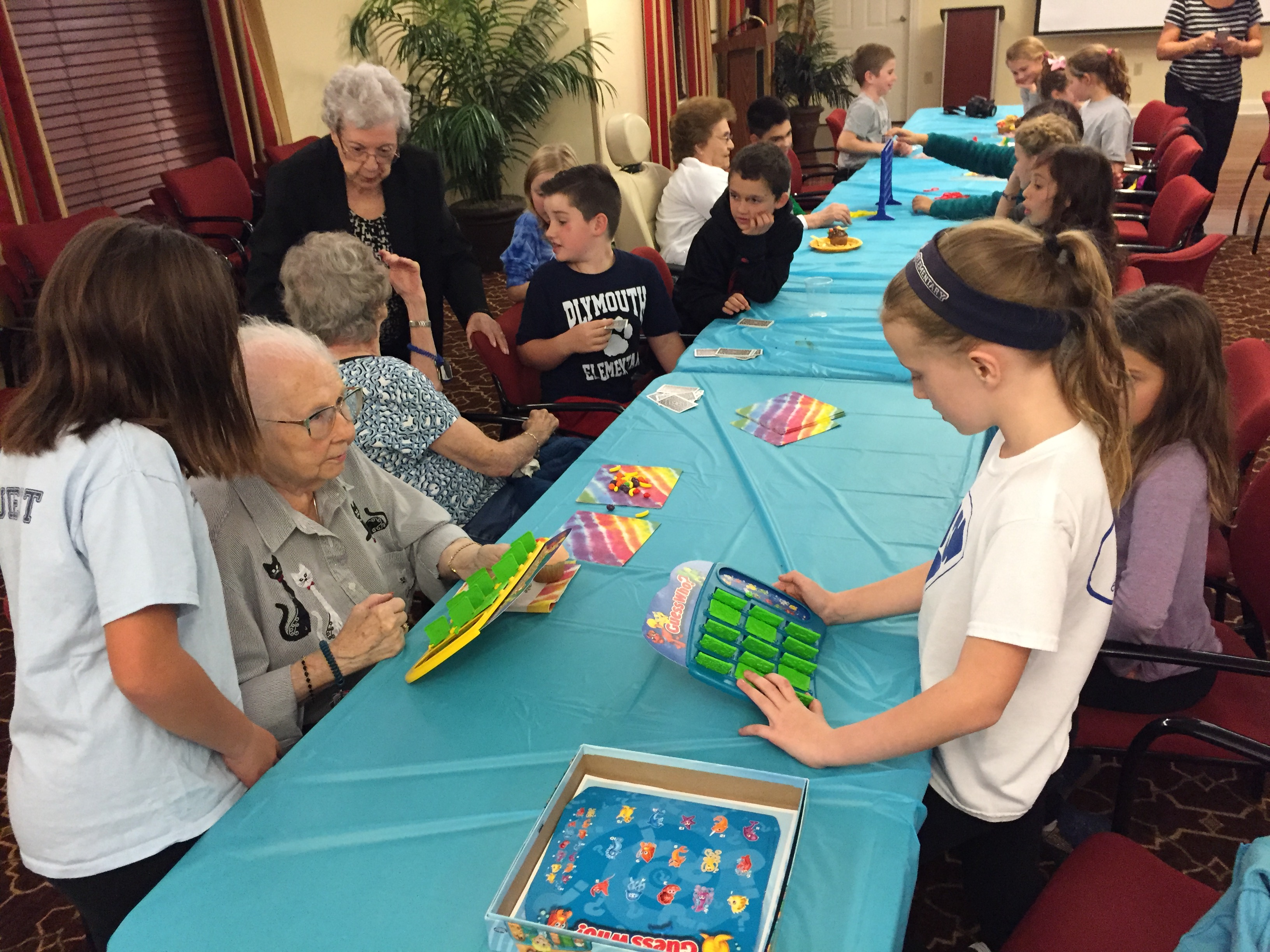 A long table with several small groups of seniors and children playing games.