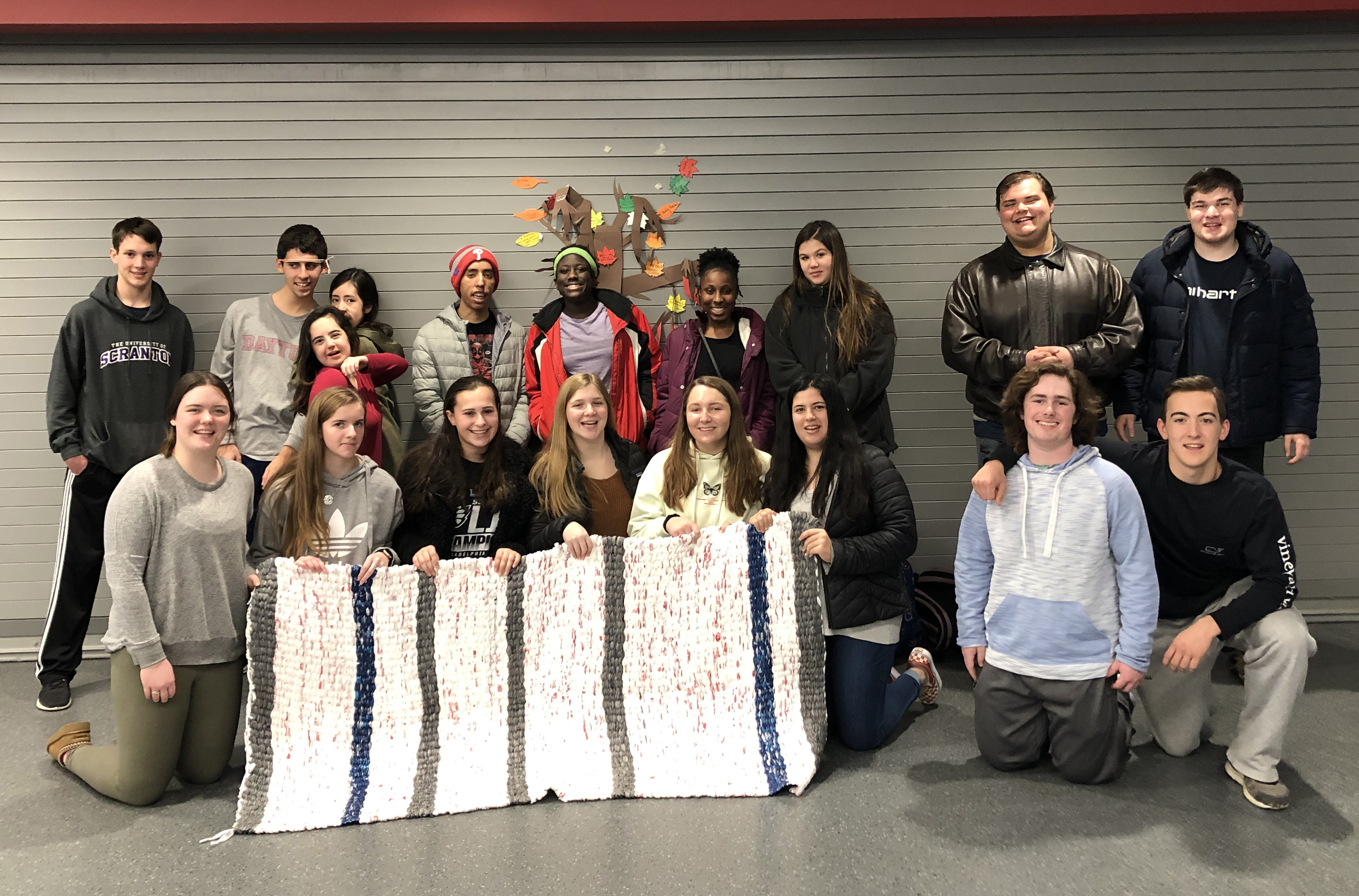 Large group of students holding a finished sleeping mat