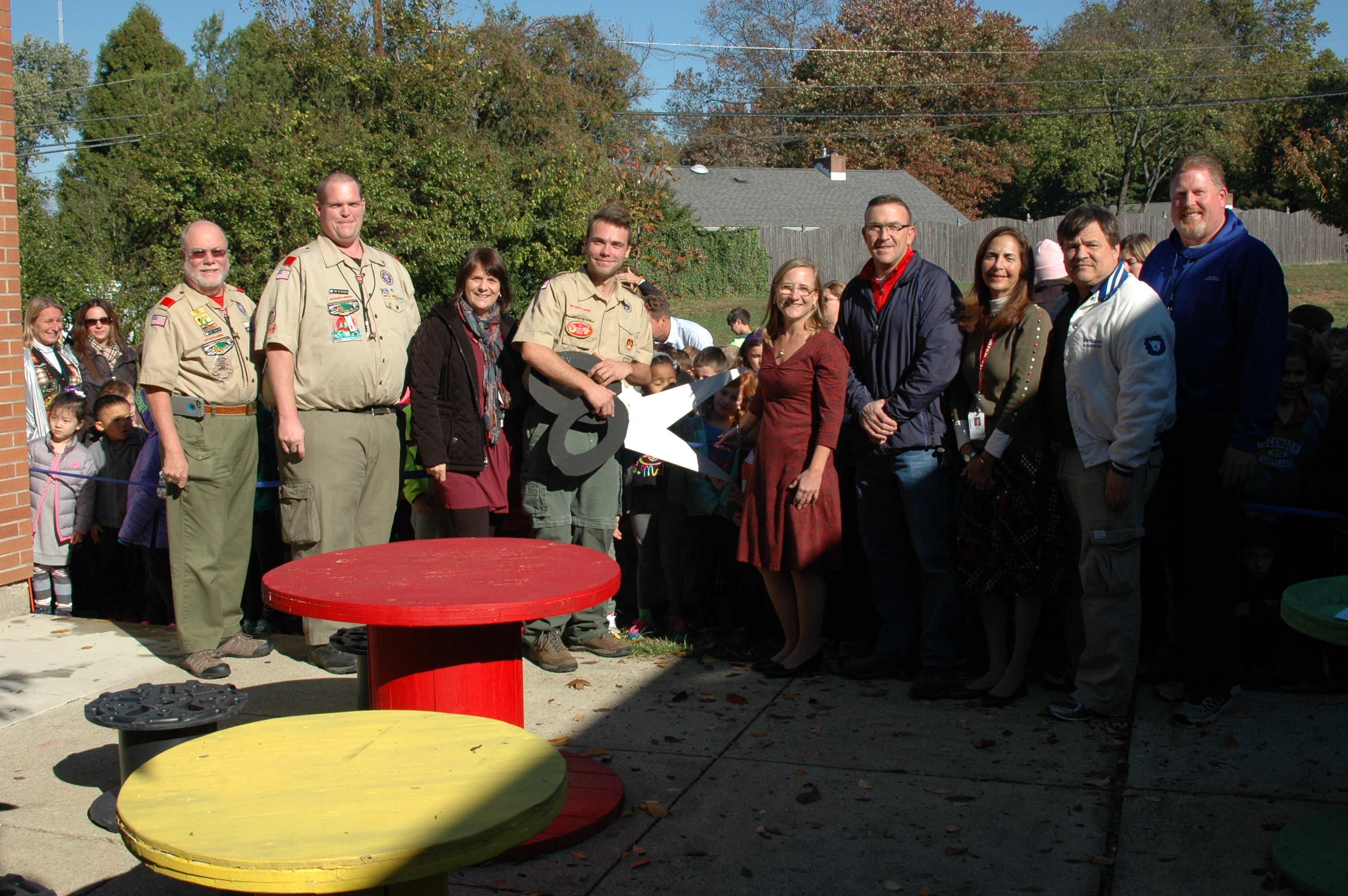Nine people standing at ribbon. One dressed in scout uniform with big cardboard scissors.