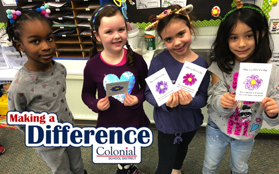 Four girls some holding cards with Making A Difference logo