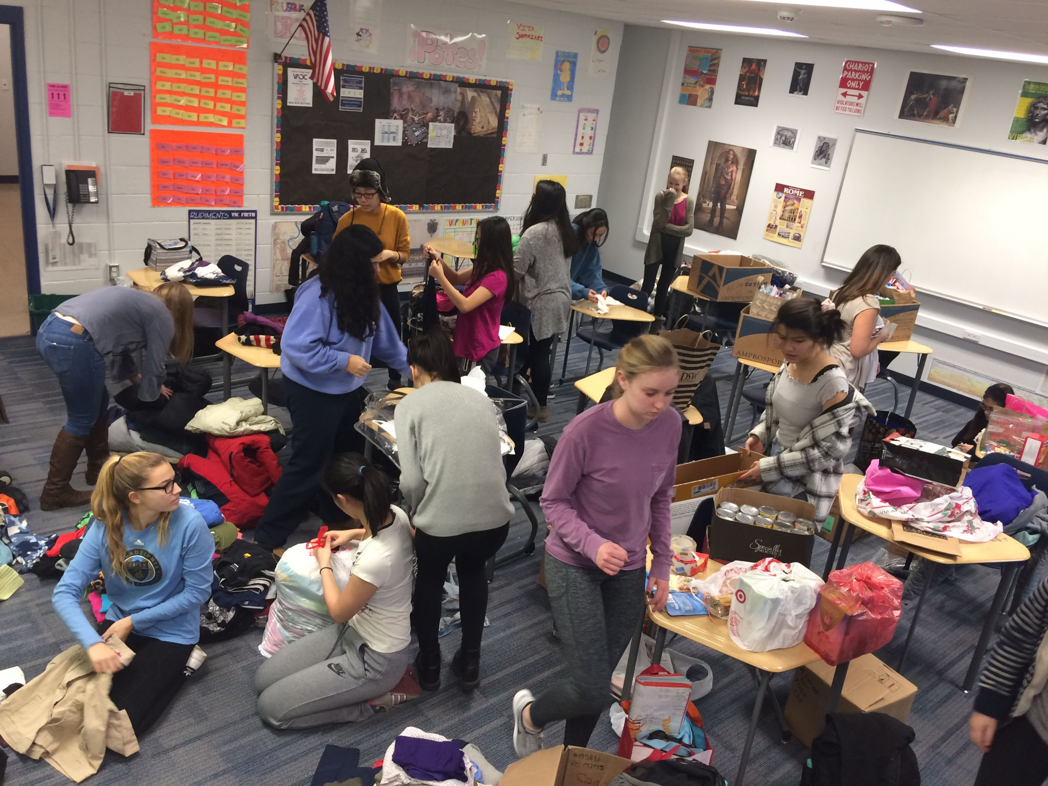 Several students organizing donations in a classroom.