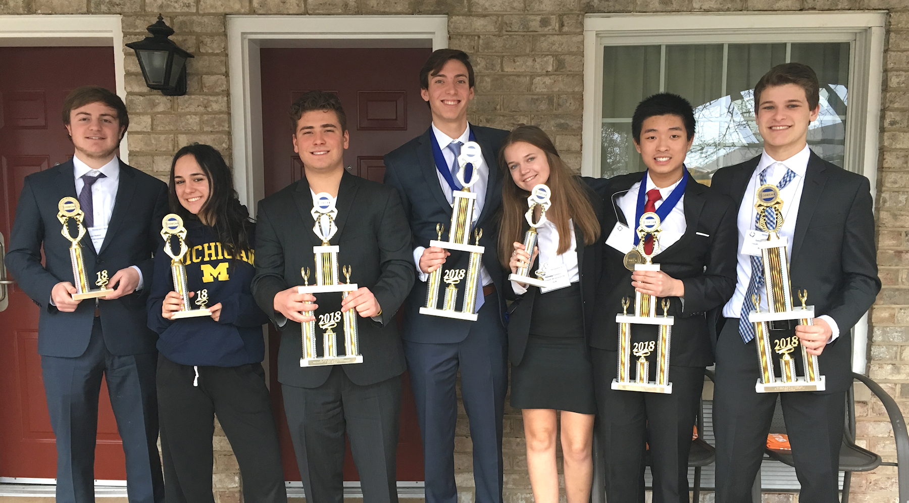 Students holding trophies from DECA state conference.