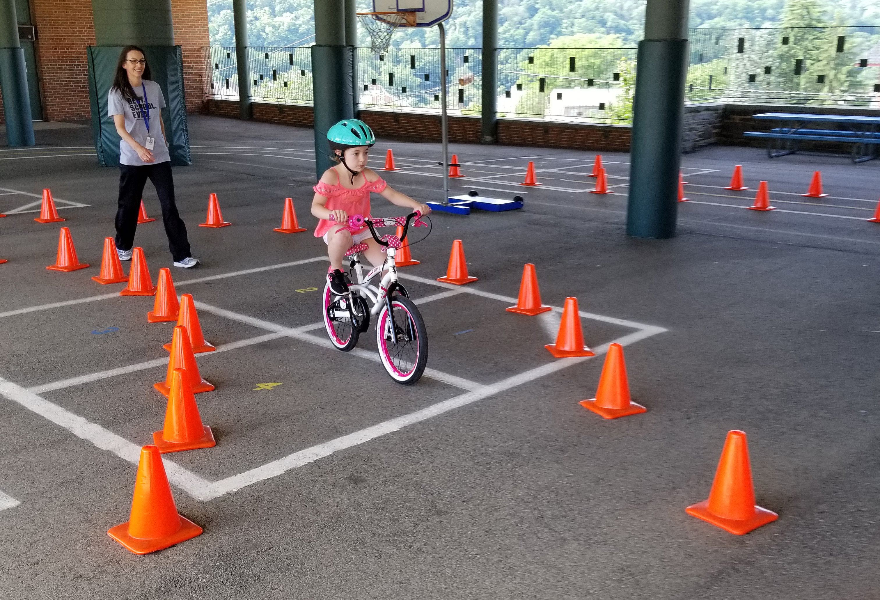 Girl on a bicycle riding a path marked by cones with a teacher watching