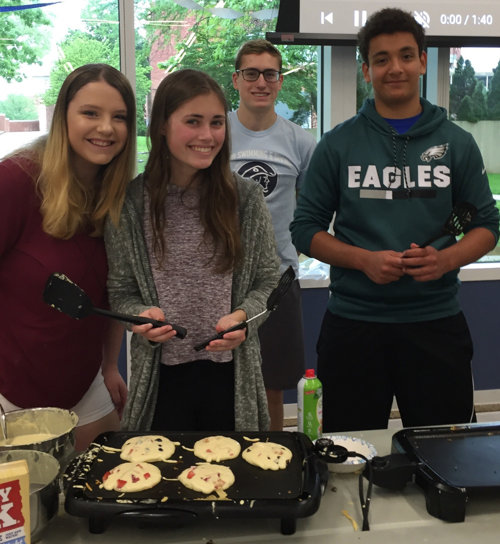 Four students making pancakes
