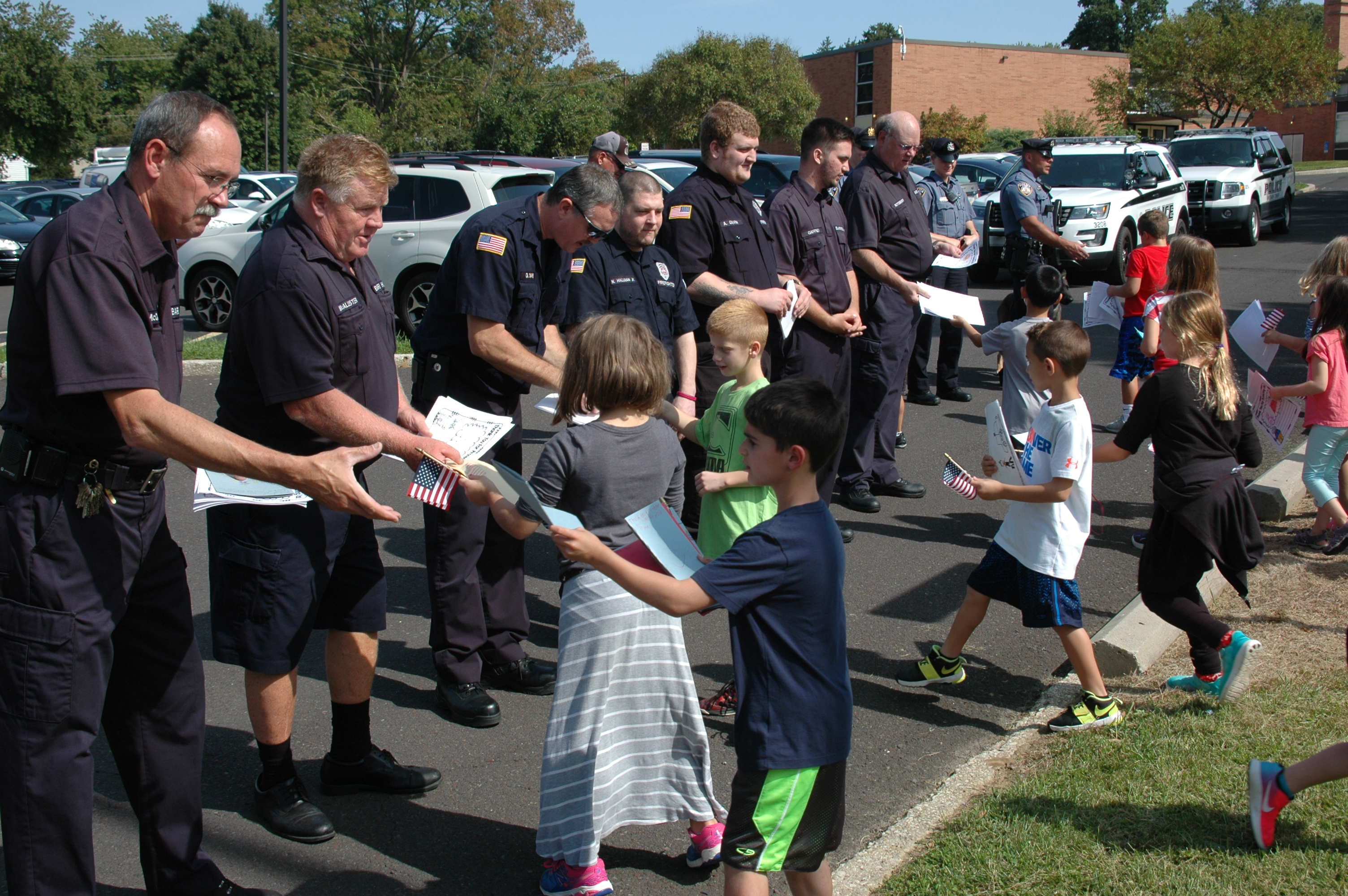 Students giving handmade thank you cards to first responders.