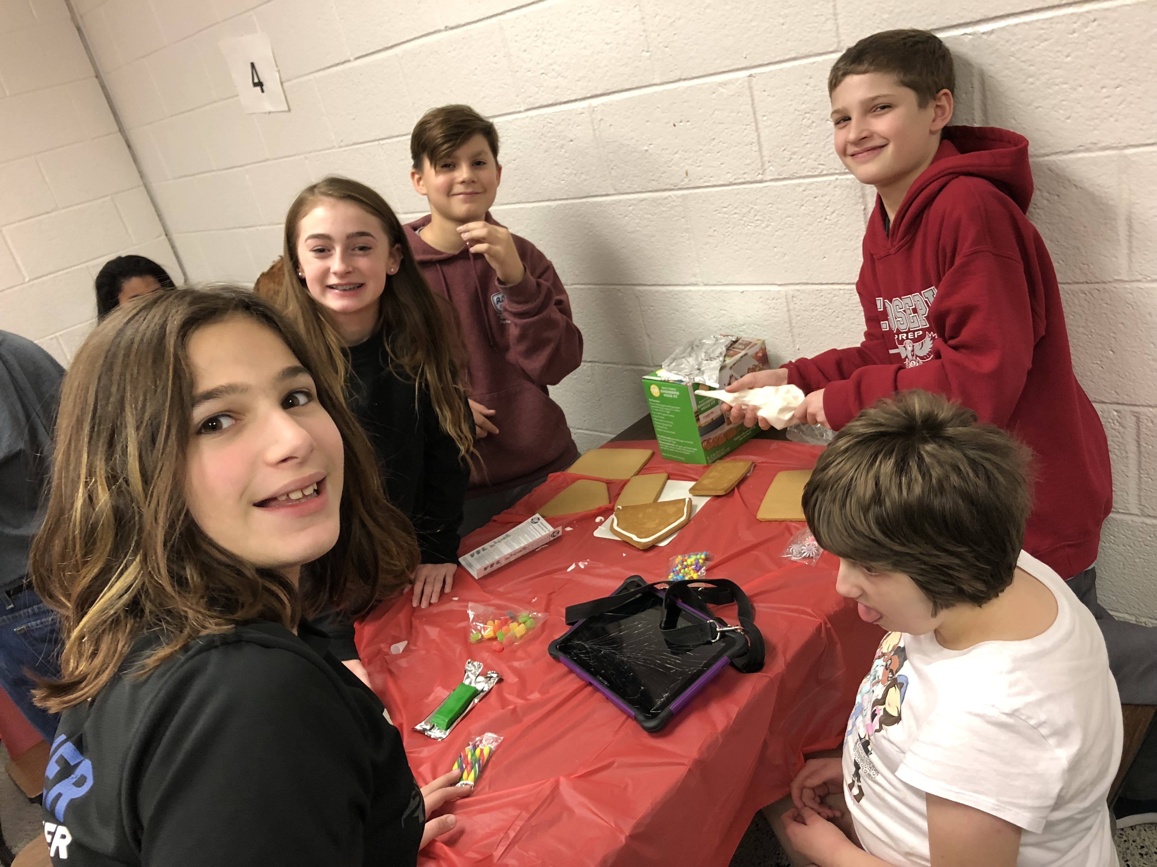 five students at table with gingerbread house parts