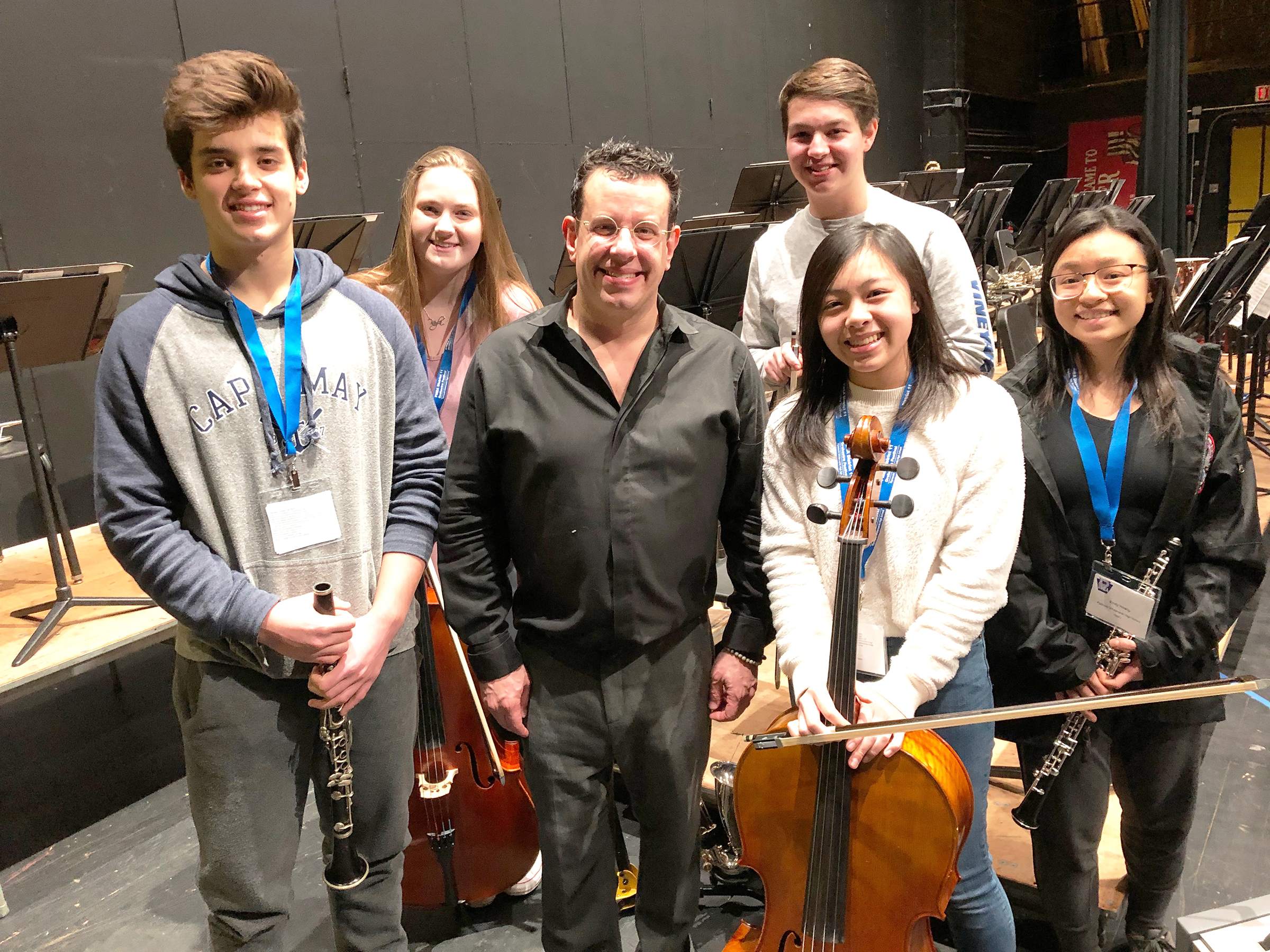 five students with instruments and the conductor
