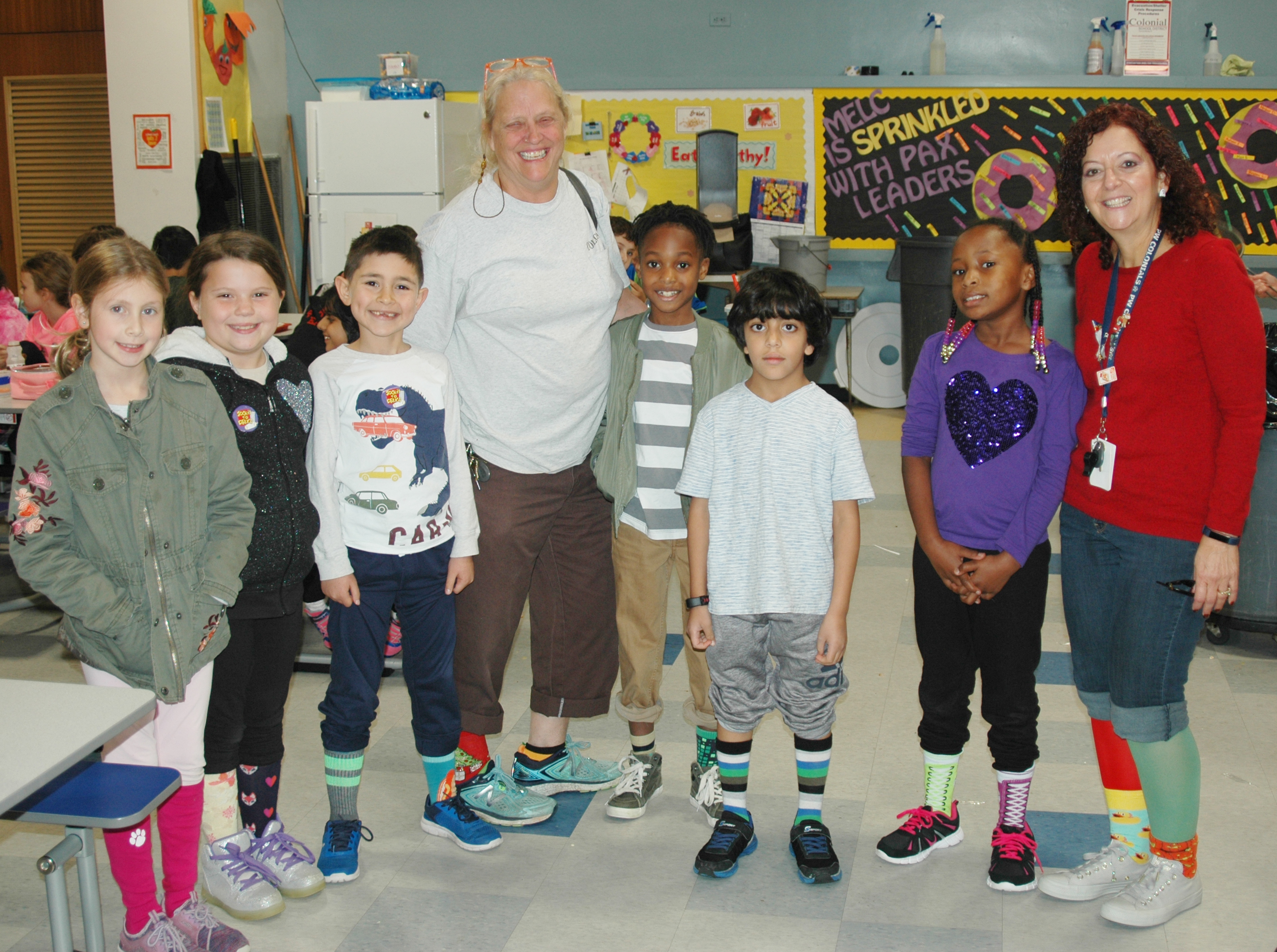 Six children and two adults with their pants rolled up to show off their brightly colored socks.