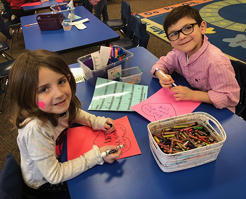 Two kids smiling at the camera while working on valentines