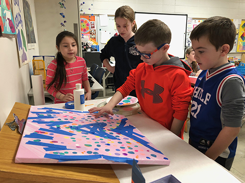 three students watching a fourth add a thumbprint to a painting