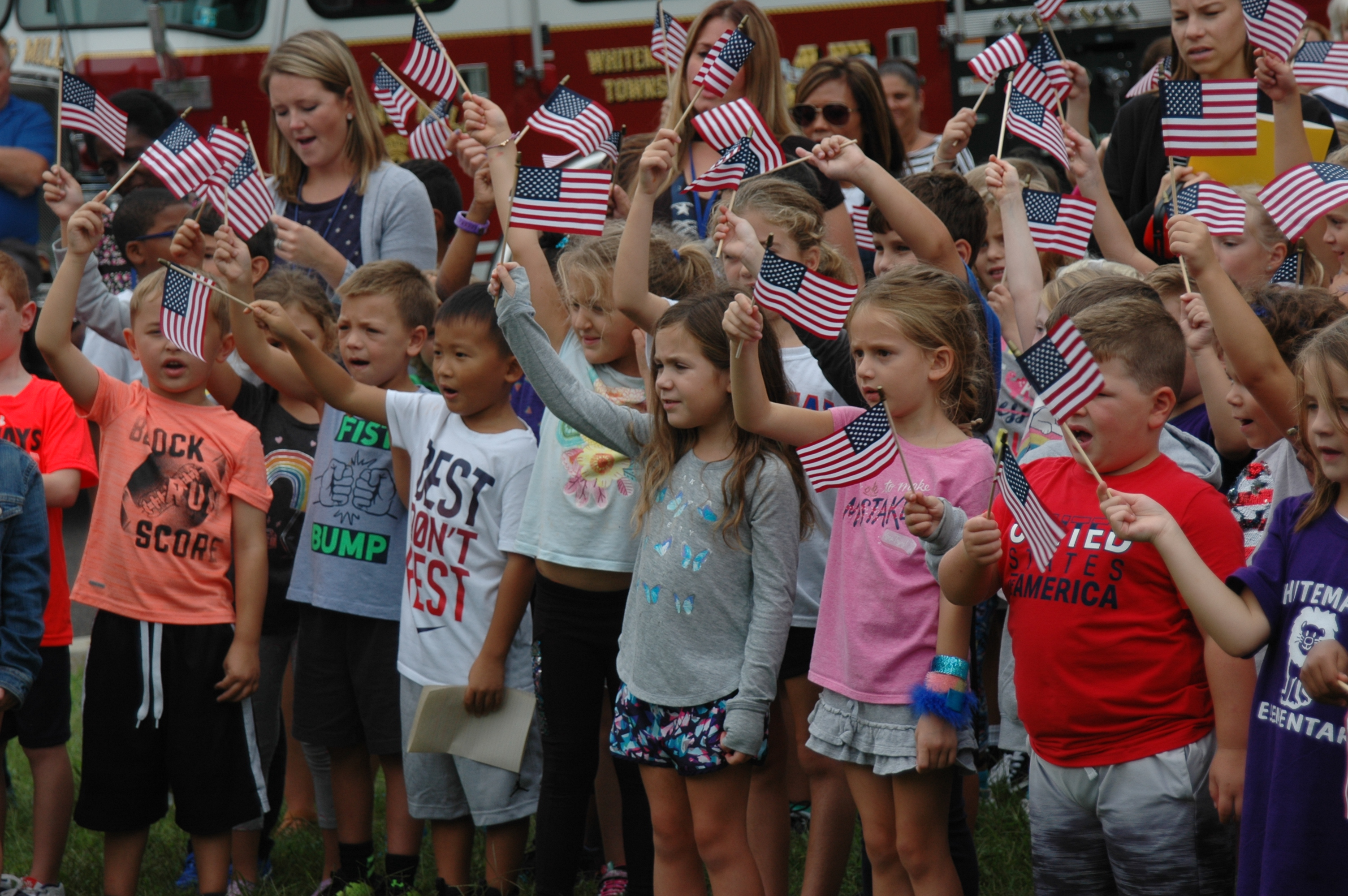 Group of children singing while waving small American flags