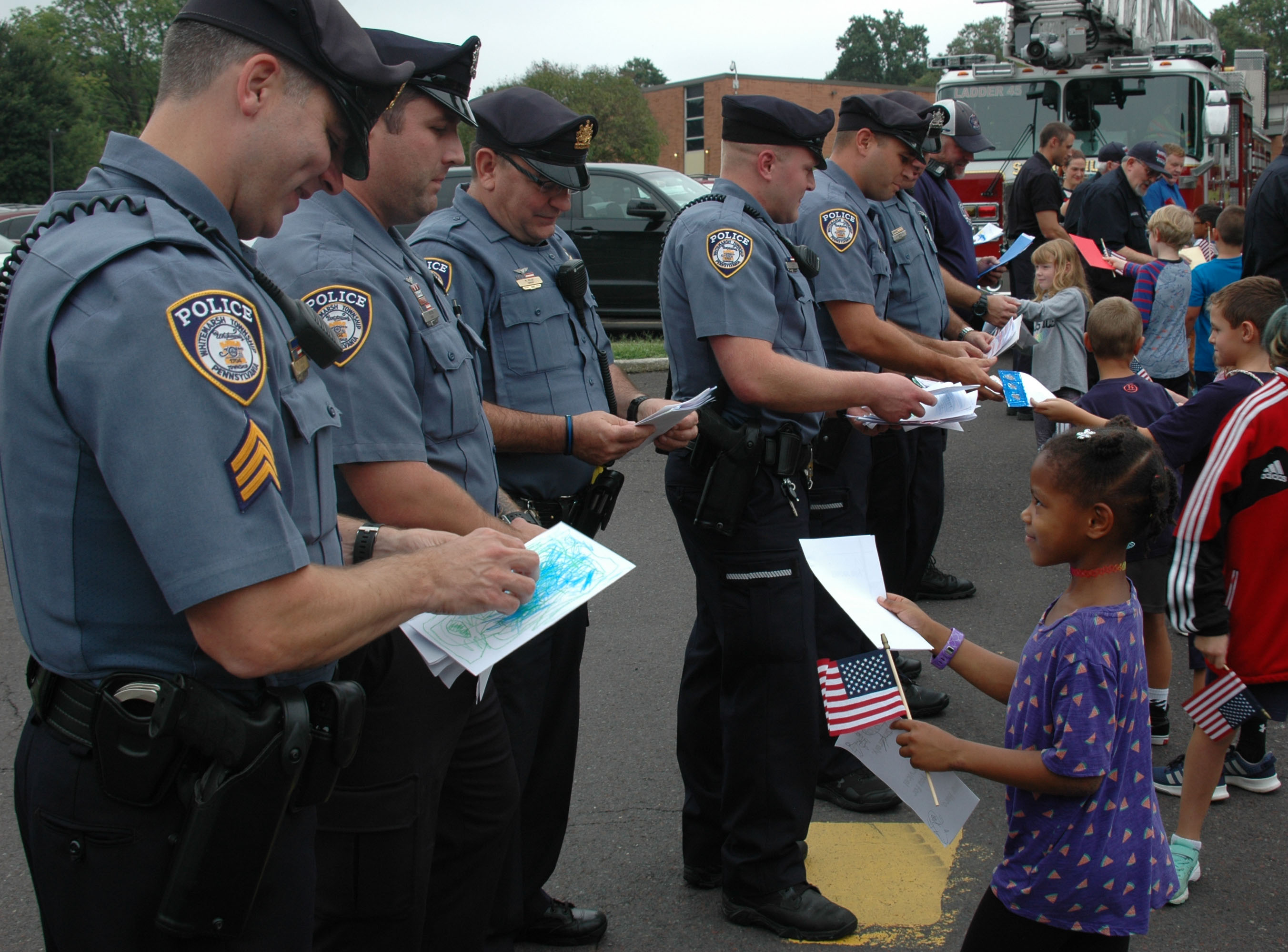 A line of a half dozen police officers being handed cards by small children