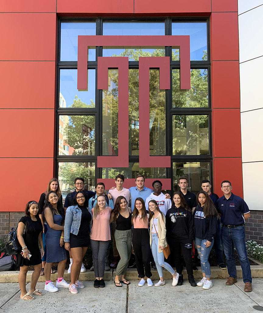 18 people standing in front of a large Temple University logo