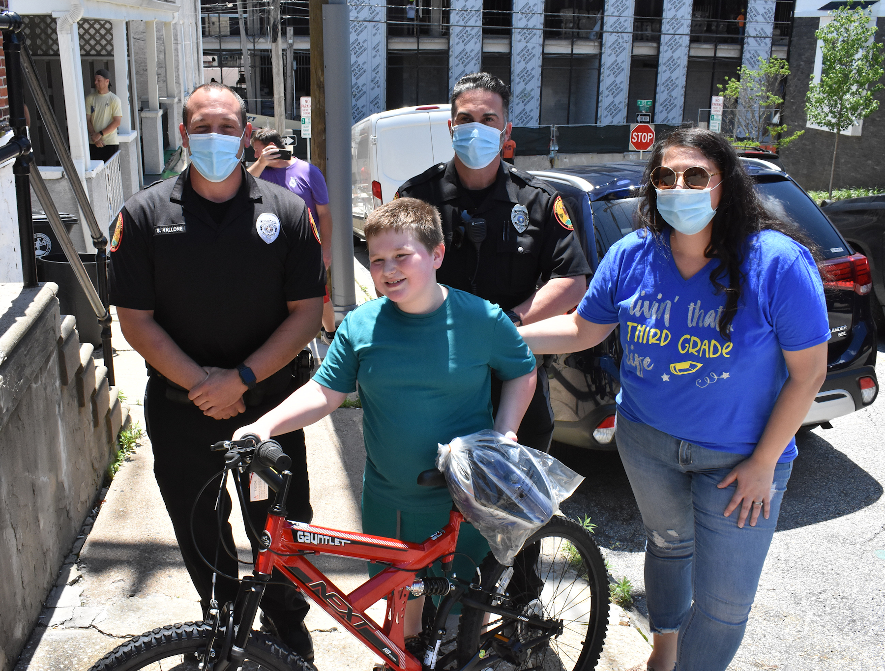 student with bicycle flanked by a teacher and two polic officers.