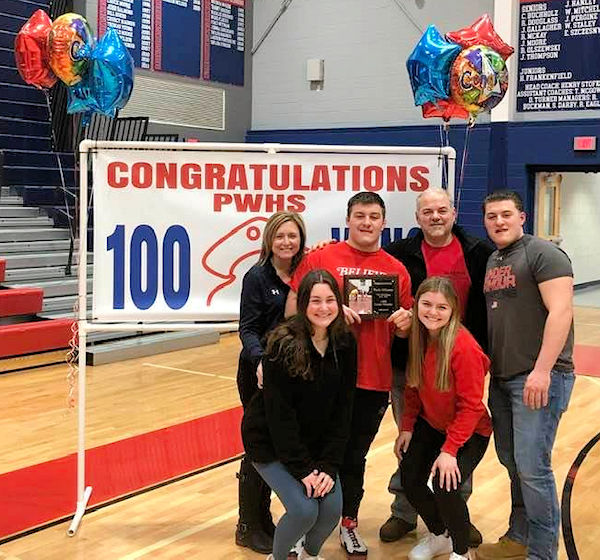 Six people standing in front of a 100 wins banner