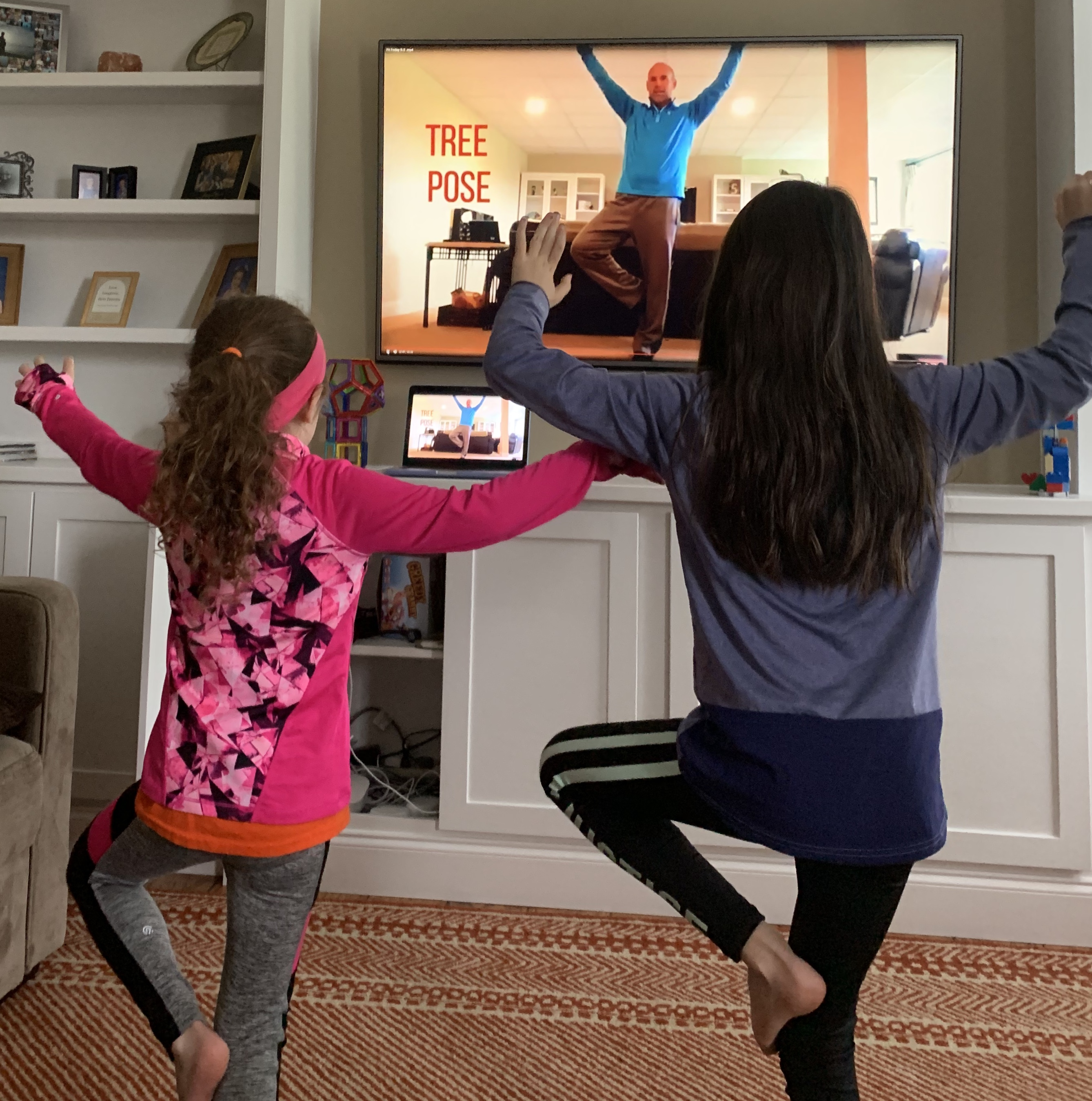 Two girls doing a standing yoga pose along with a man on TV