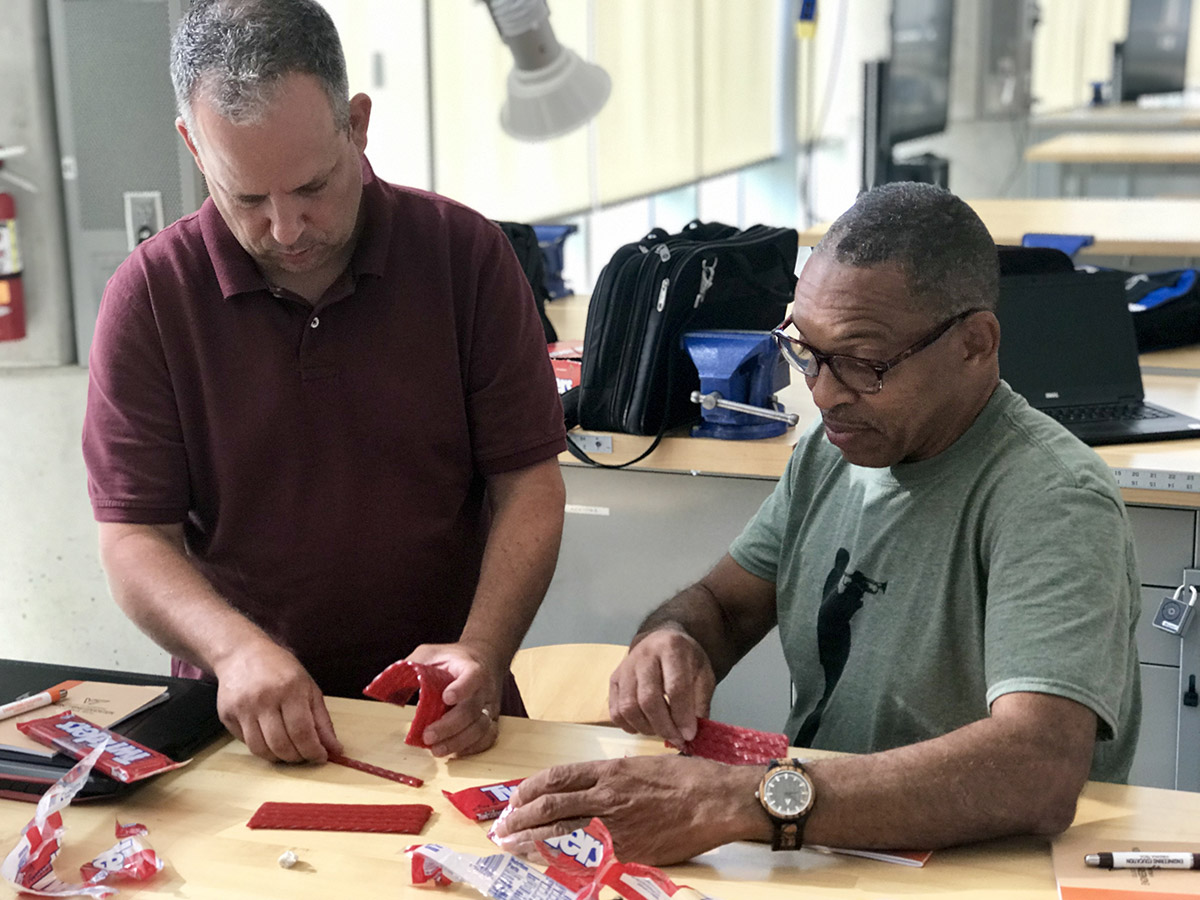 Two men building structure out of licorice