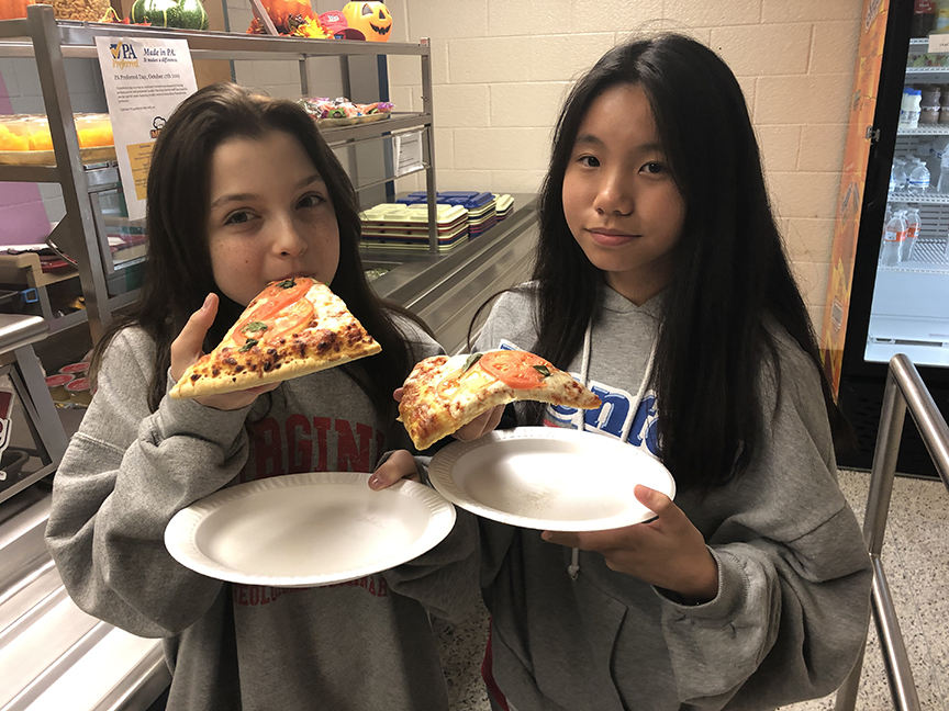 two girls with pizza slices