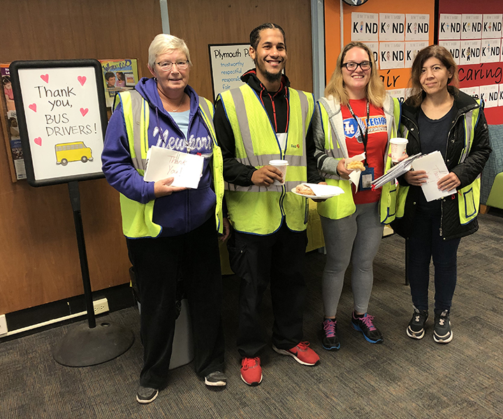 Four adults wearing safety vests. Two holding breakfast items. Two holding thank you cards.