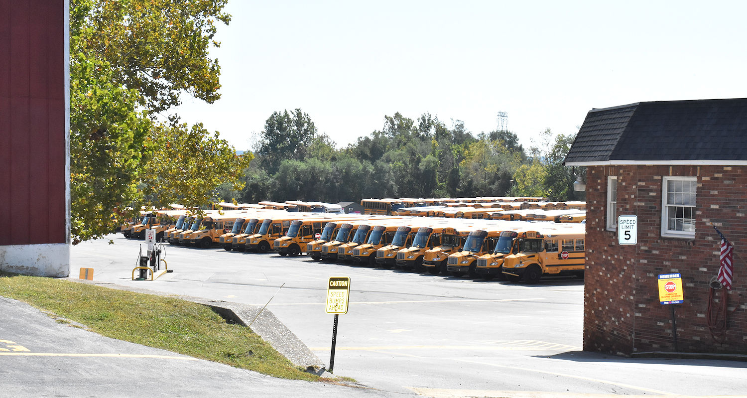 Photos of parking lot with rows of parked buses