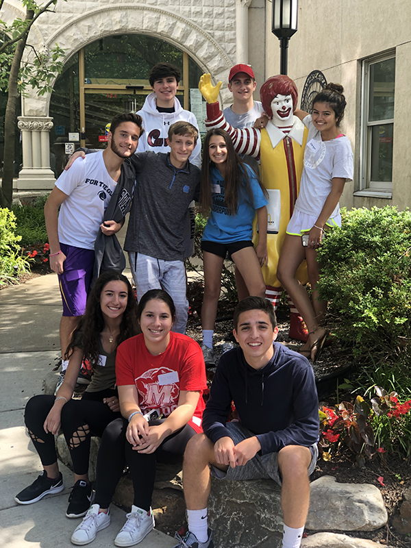 Nine high school students with statue of Ronald McDonald