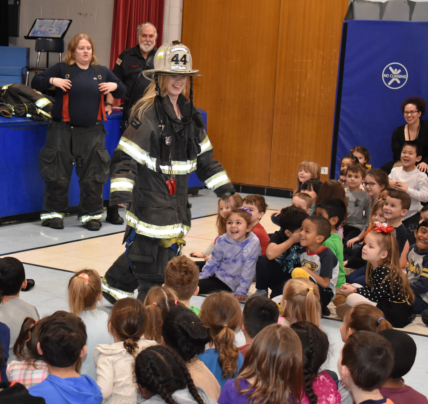 Female teacher wearing firefighting suit greets students.