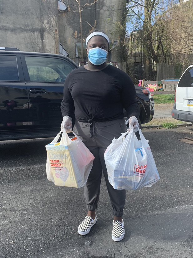 high school girl wearing mask and carrying two large bags of groceries