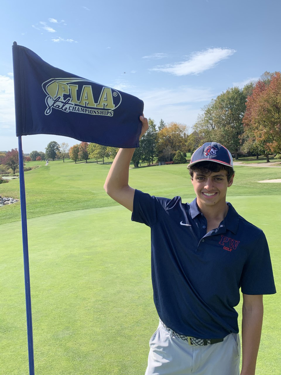 Boy on golf course holding PIAA State Championships flag