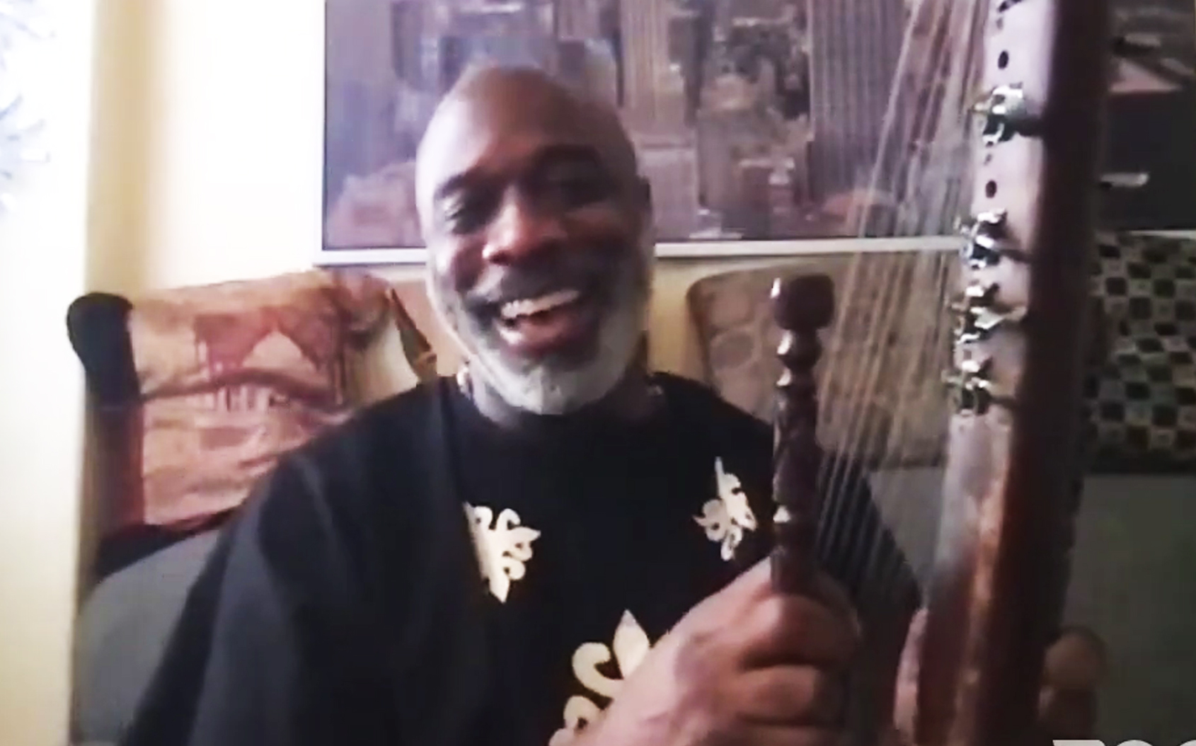 smiling man holding exotic stringed instrument