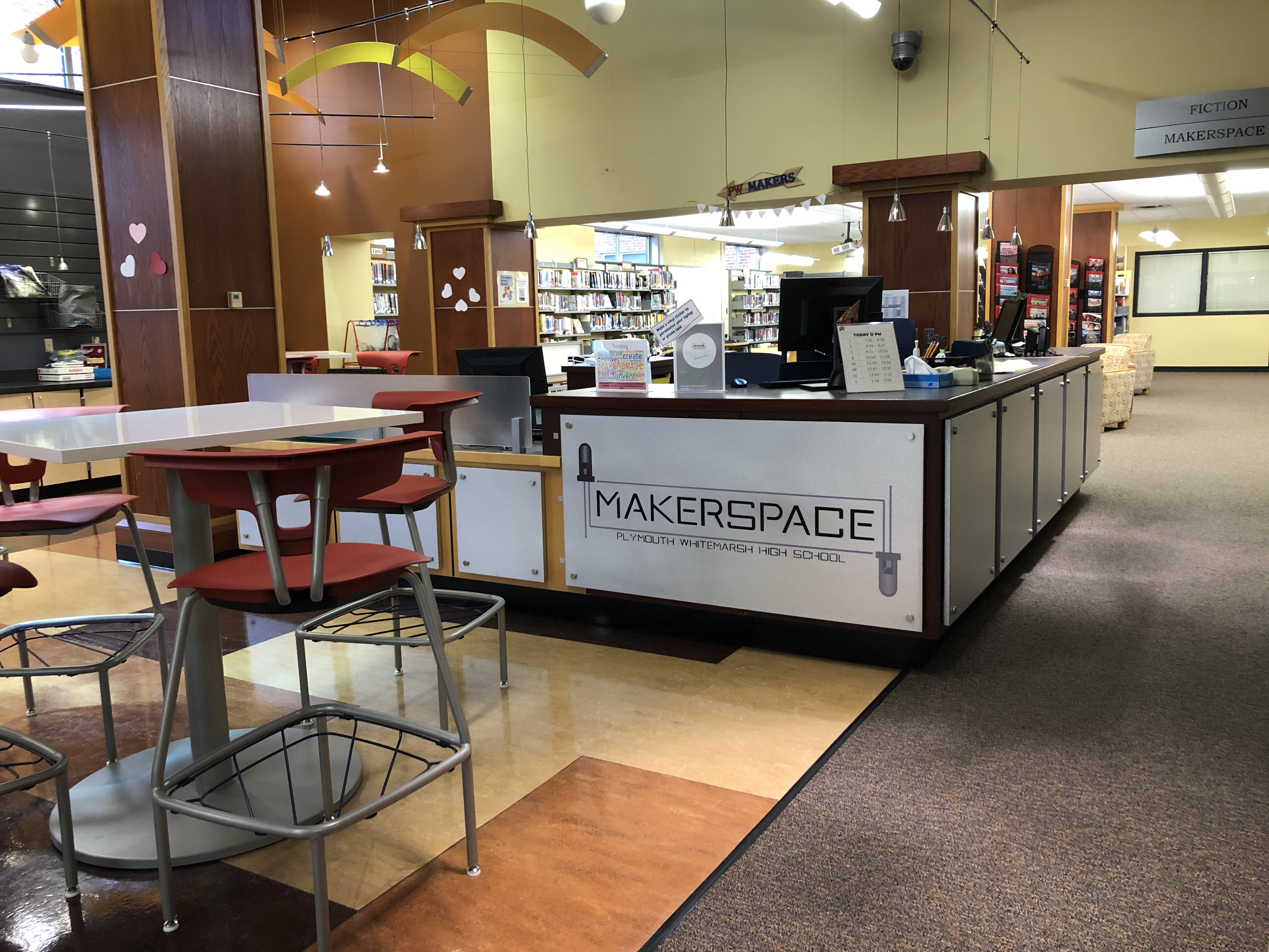 front desk of library and part of the seating area with makerspace logo