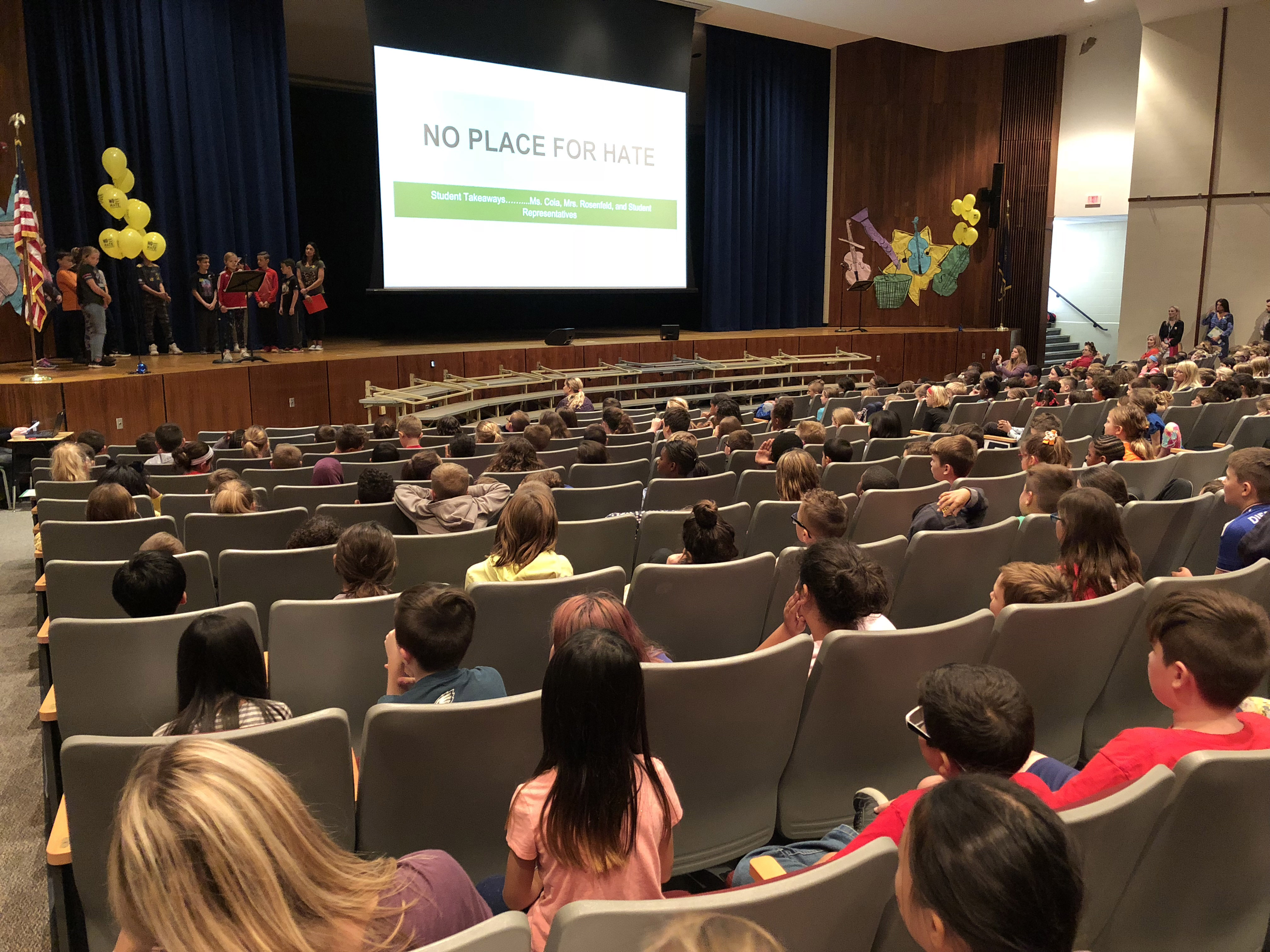 Auditorium of kids looking at students on stage with No Place for Hate on screen