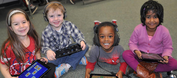 Four kindergarteners on the floor with tablets