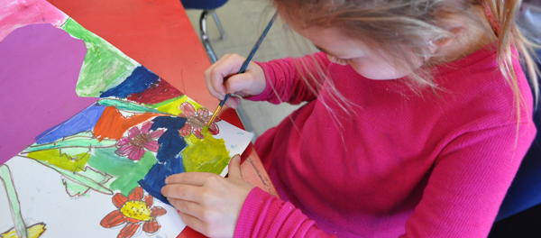 An elementary student painting a picture of flowers